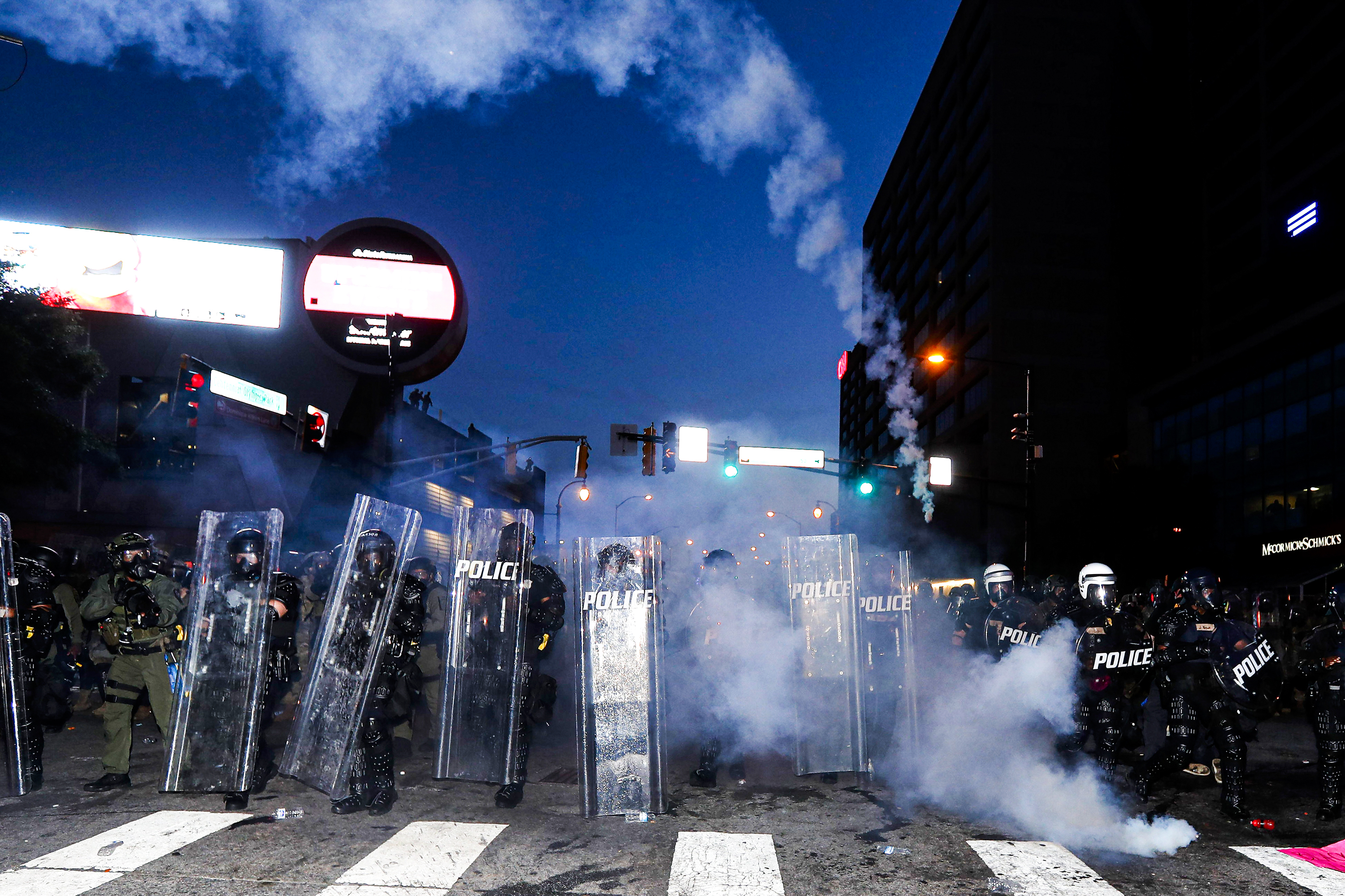 "Under a electronic billboard and traffic lights illuminating a white crosswalk, officers in black body armor, bearing tall plastic shields reading ""Police"" fire tear gas towards the camera, the trail of a canister forming an arc across the frame."