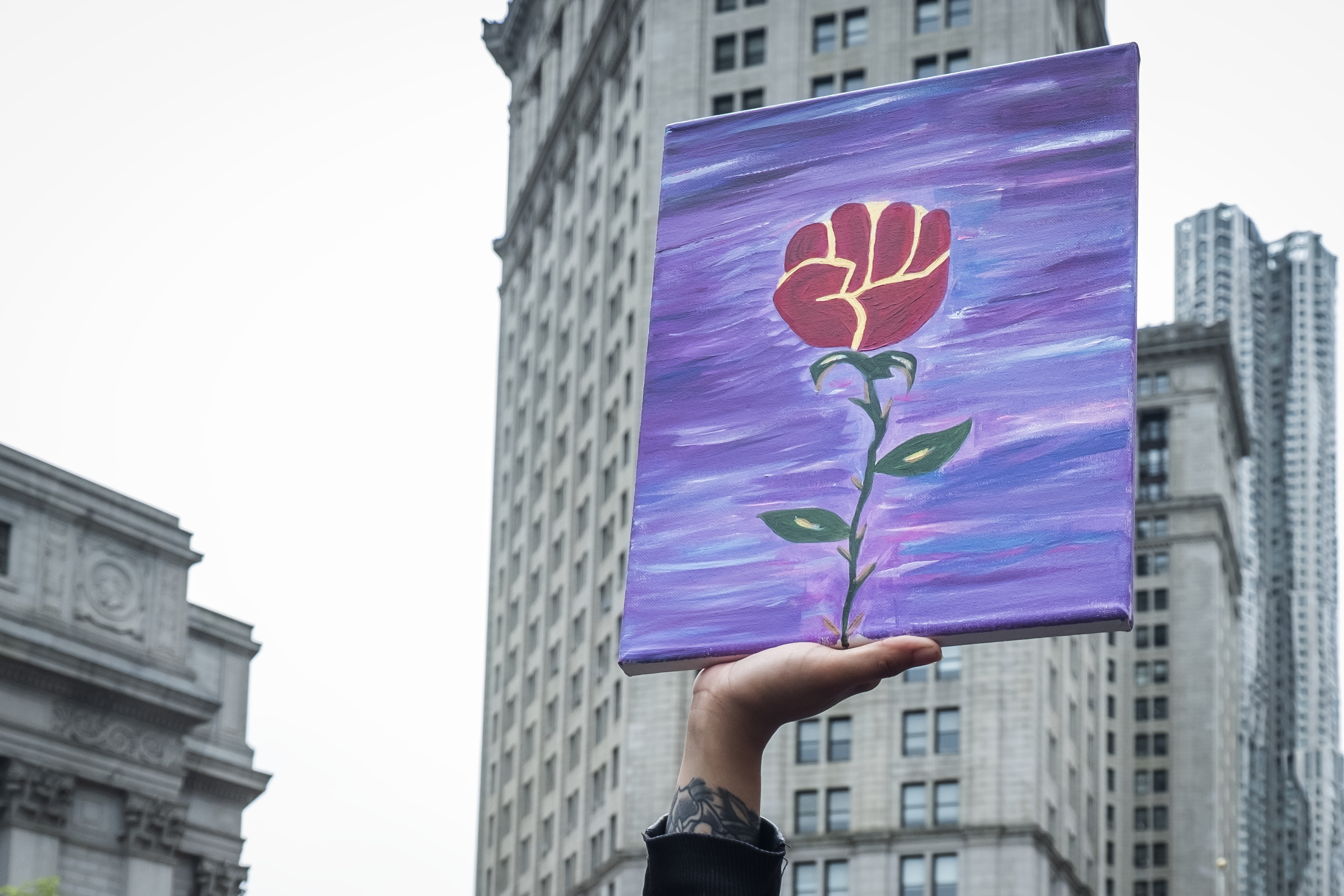 A protester carries a hand painted picture of a red fist in the air at the top of a flower made to resemble a rose.