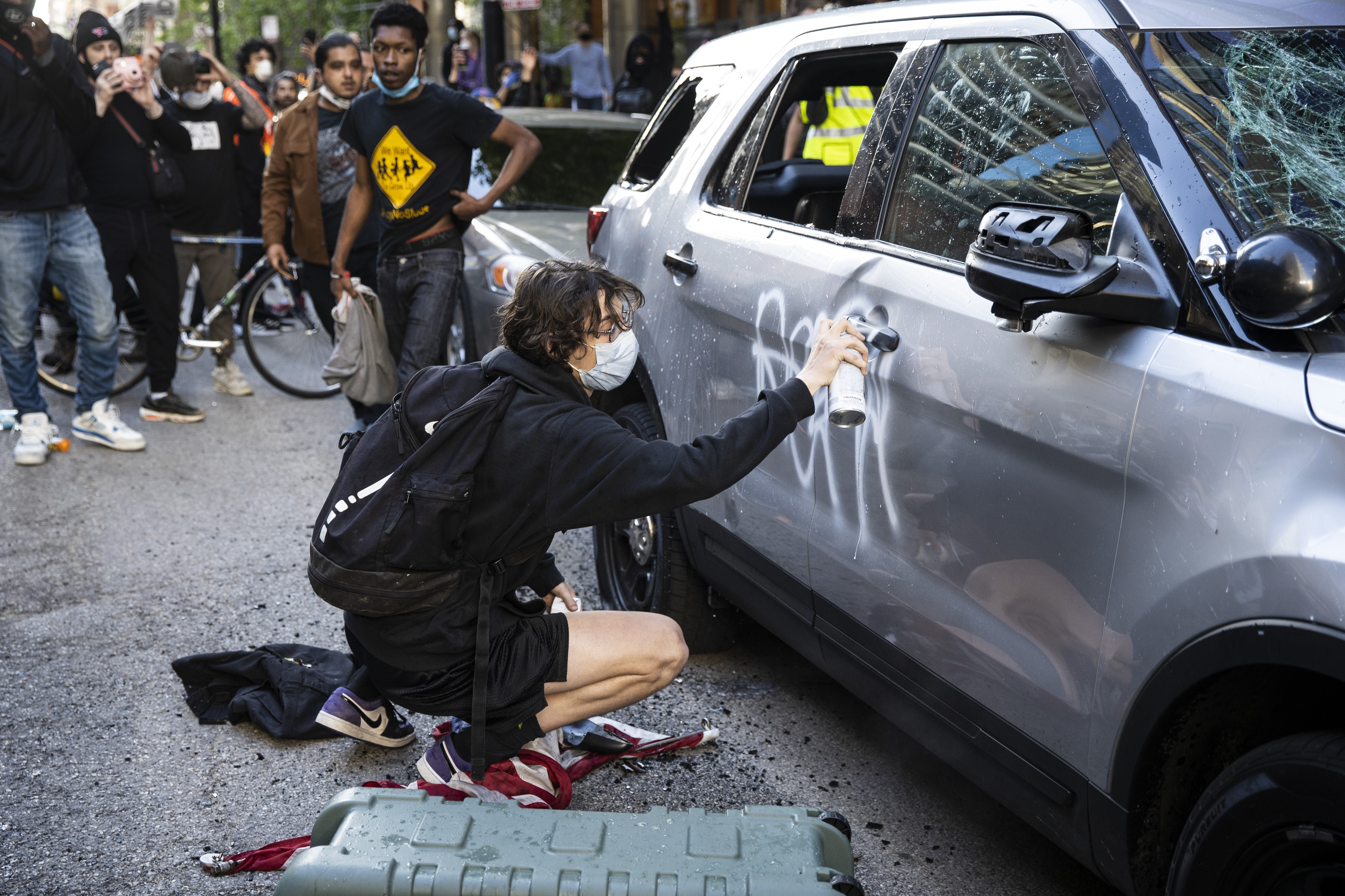 A protester sprays paint on a Chicago Police Department SUV on Kinzie Street near State Street on Saturday. Thousands of protesters in Chicago over several days have joined national outrage over the death of George Floyd, who died in police custody on Memorial Day in Minneapolis.