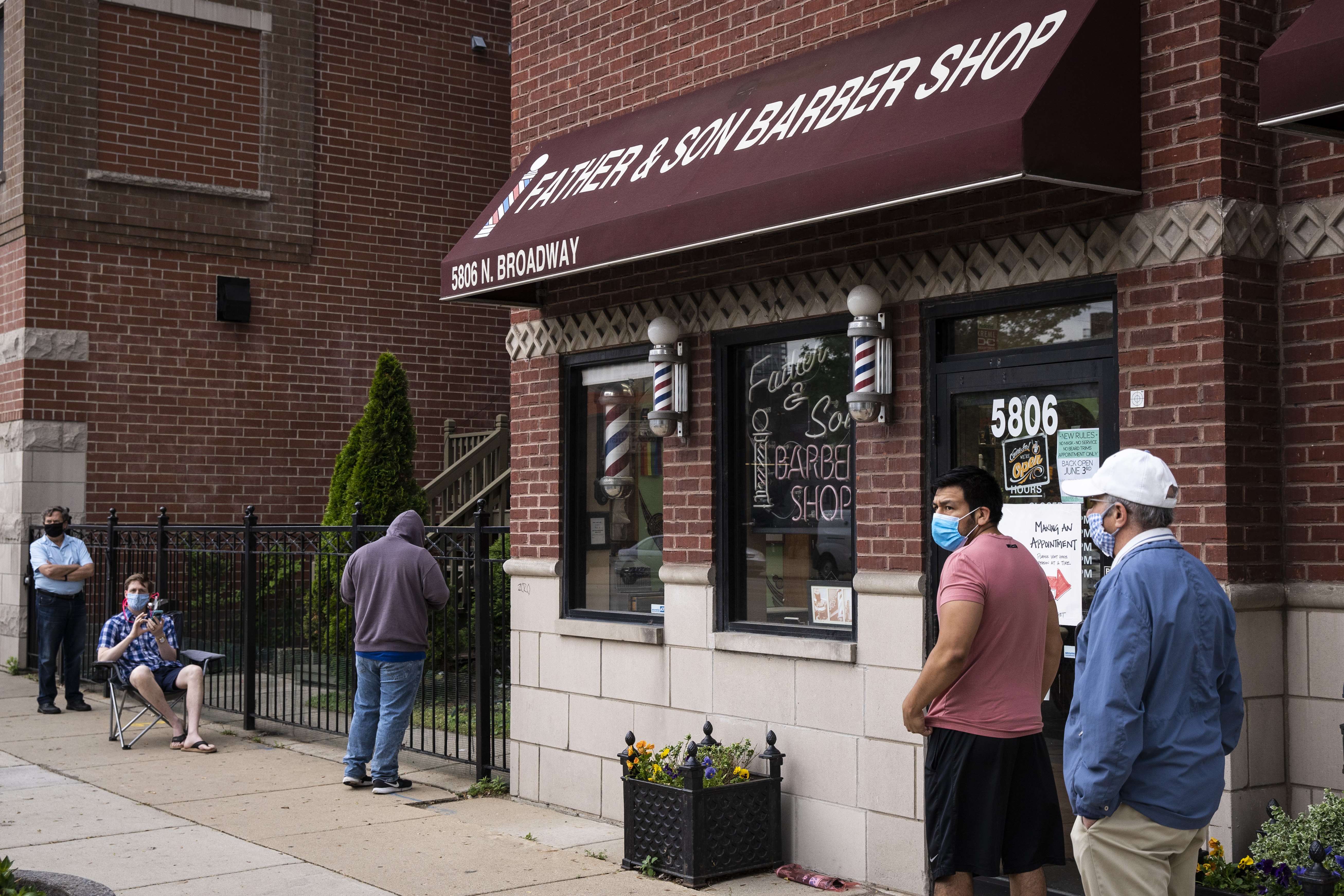 Men wait in line outside Father & Son Barber Shop at 5806 N. Broadway St. in Edgewater, Wednesday morning, June 3, 2020.