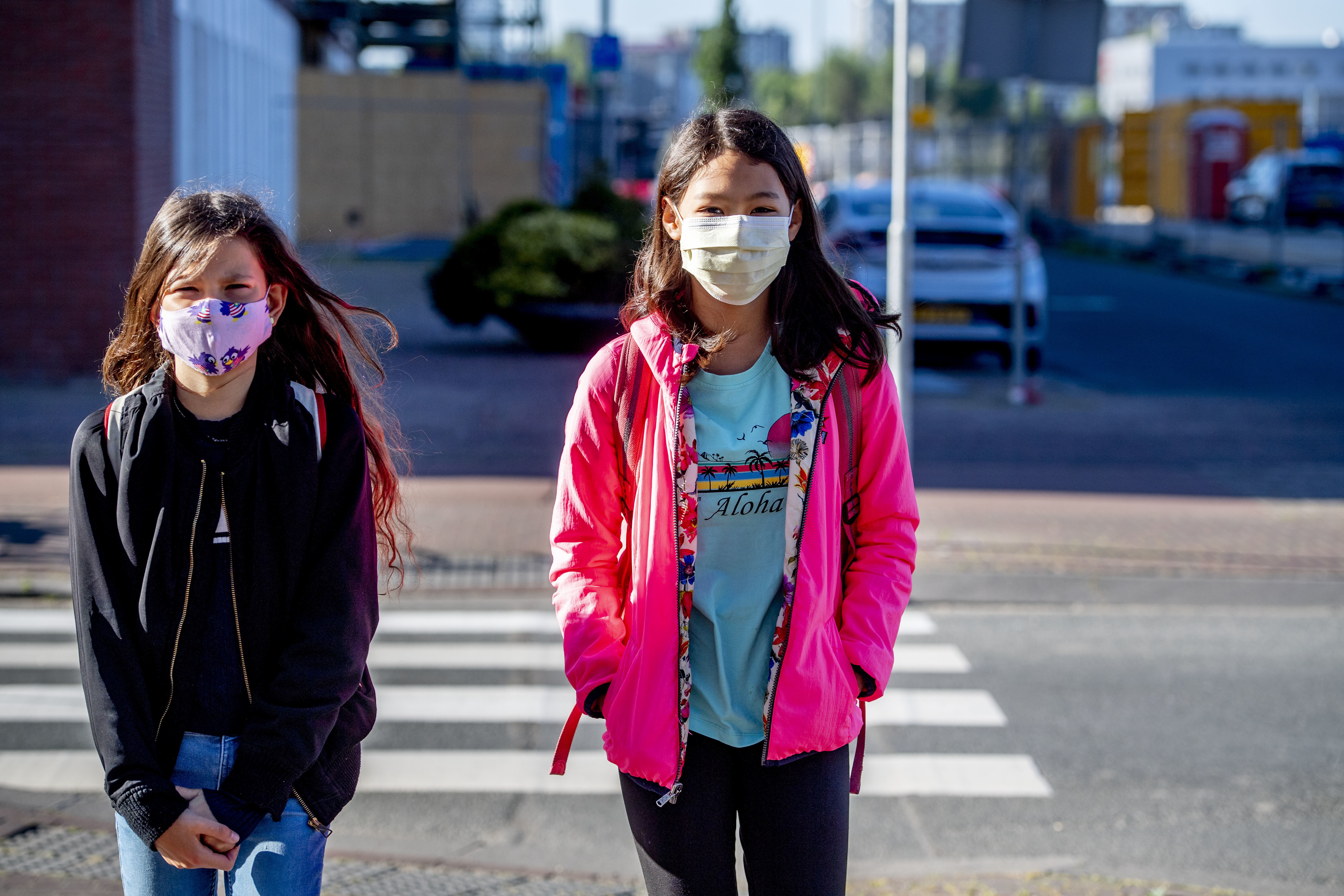 Children walk to school while wearing face masks as a...