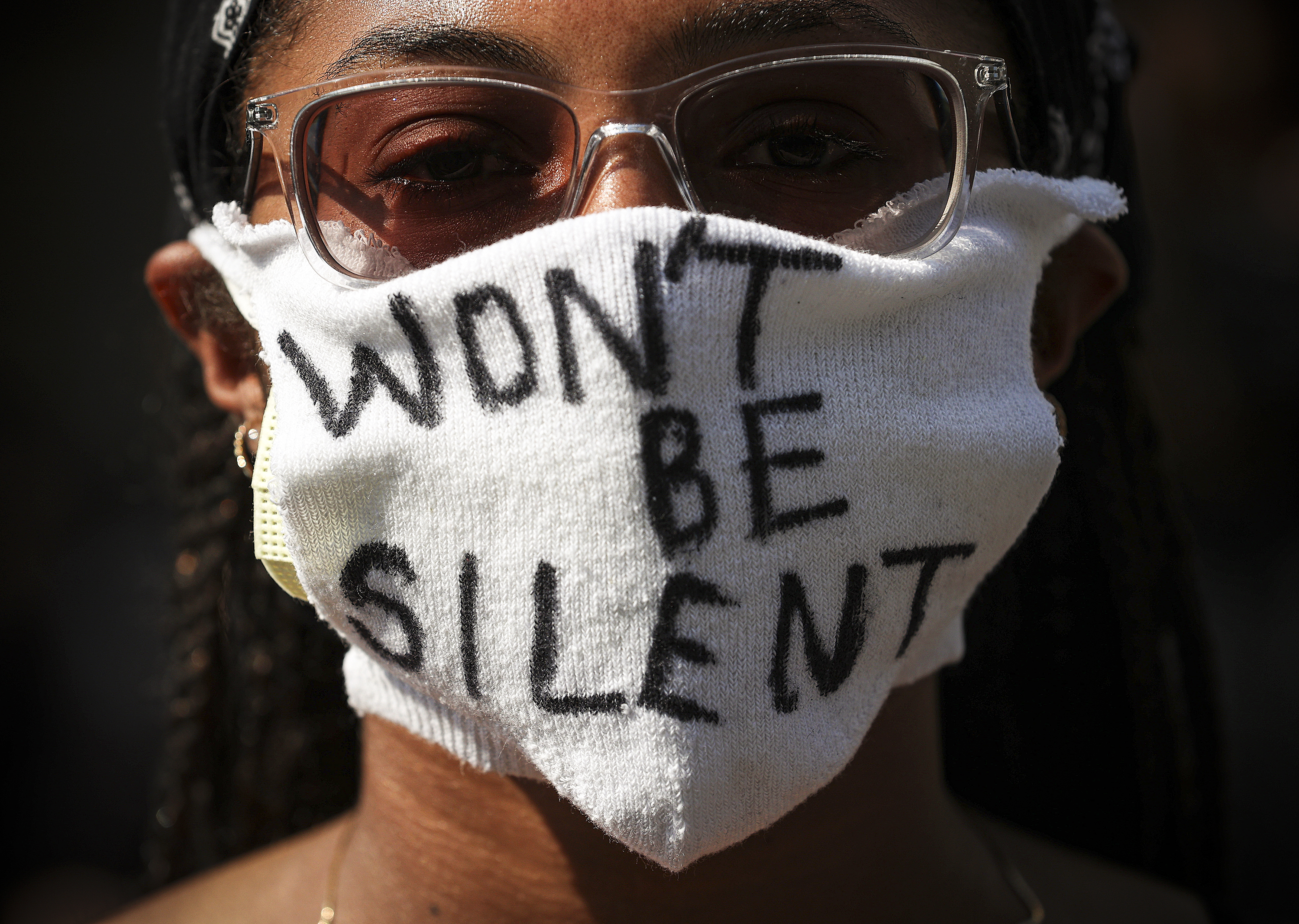 "A portrait of a black woman in a white face mask. Her mask is pulled up just below her glasses. On it, she has written in black ink, ""Won't be silent."""