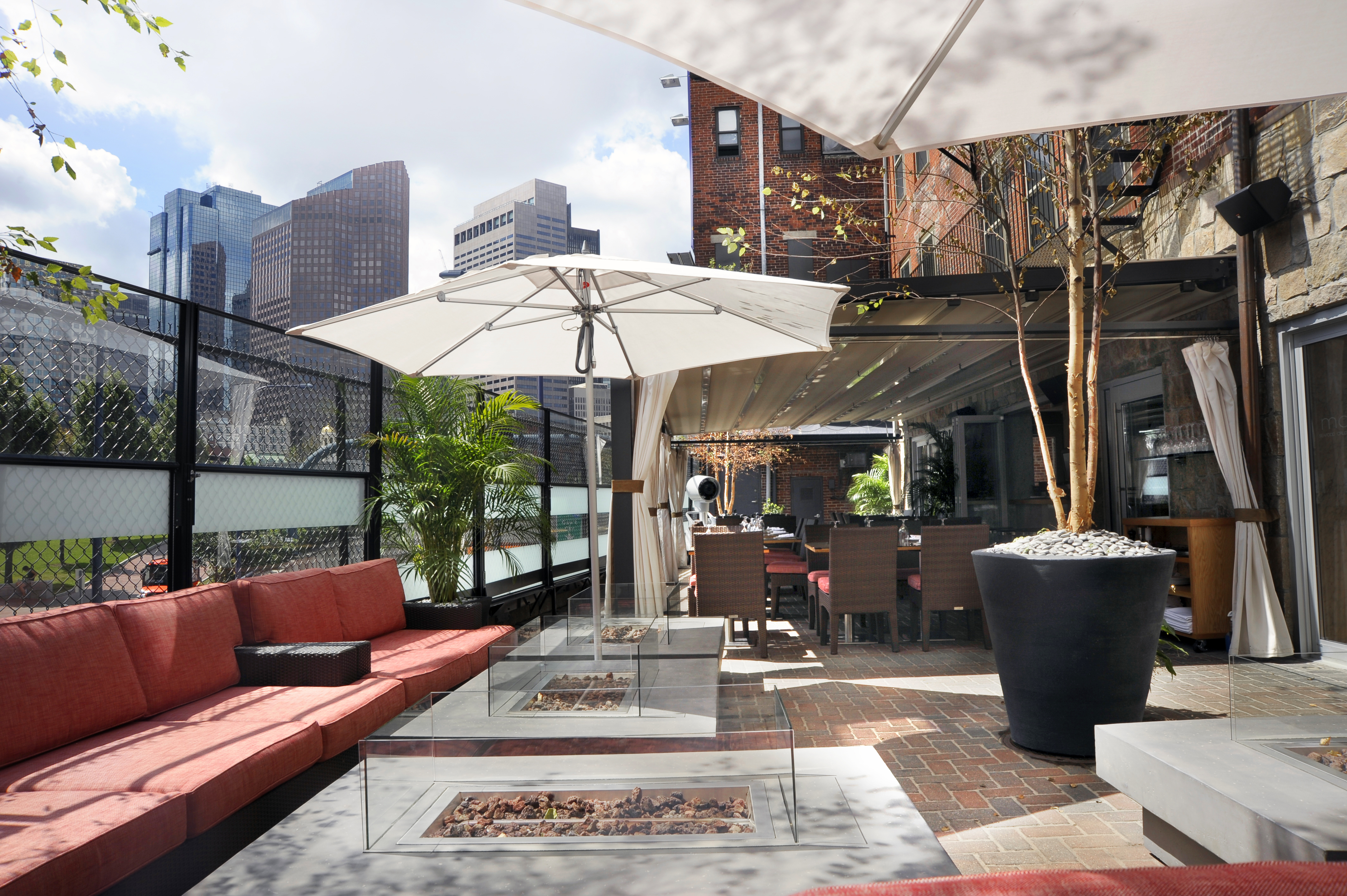 A restaurant's outdoor patio with fire pits, white umbrellas, and lounge seating with red cushions
