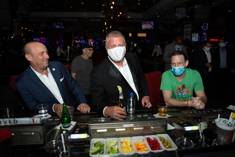 Three men stand at a bar