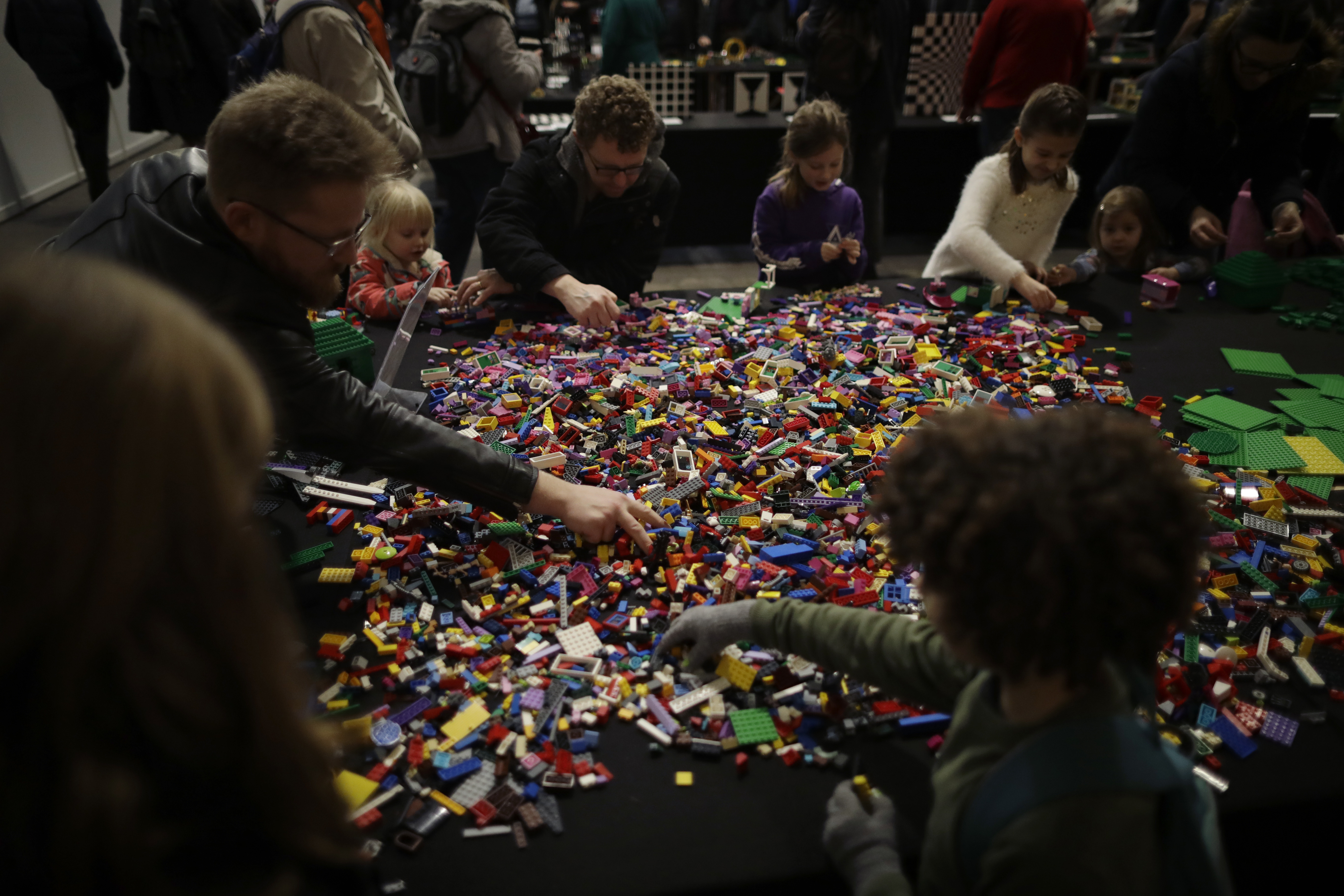 Children and adults play with Lego on a stand at the London Model Engineering Exhibition at Alexandra Palace in north London, Friday, Jan. 17, 2020.
