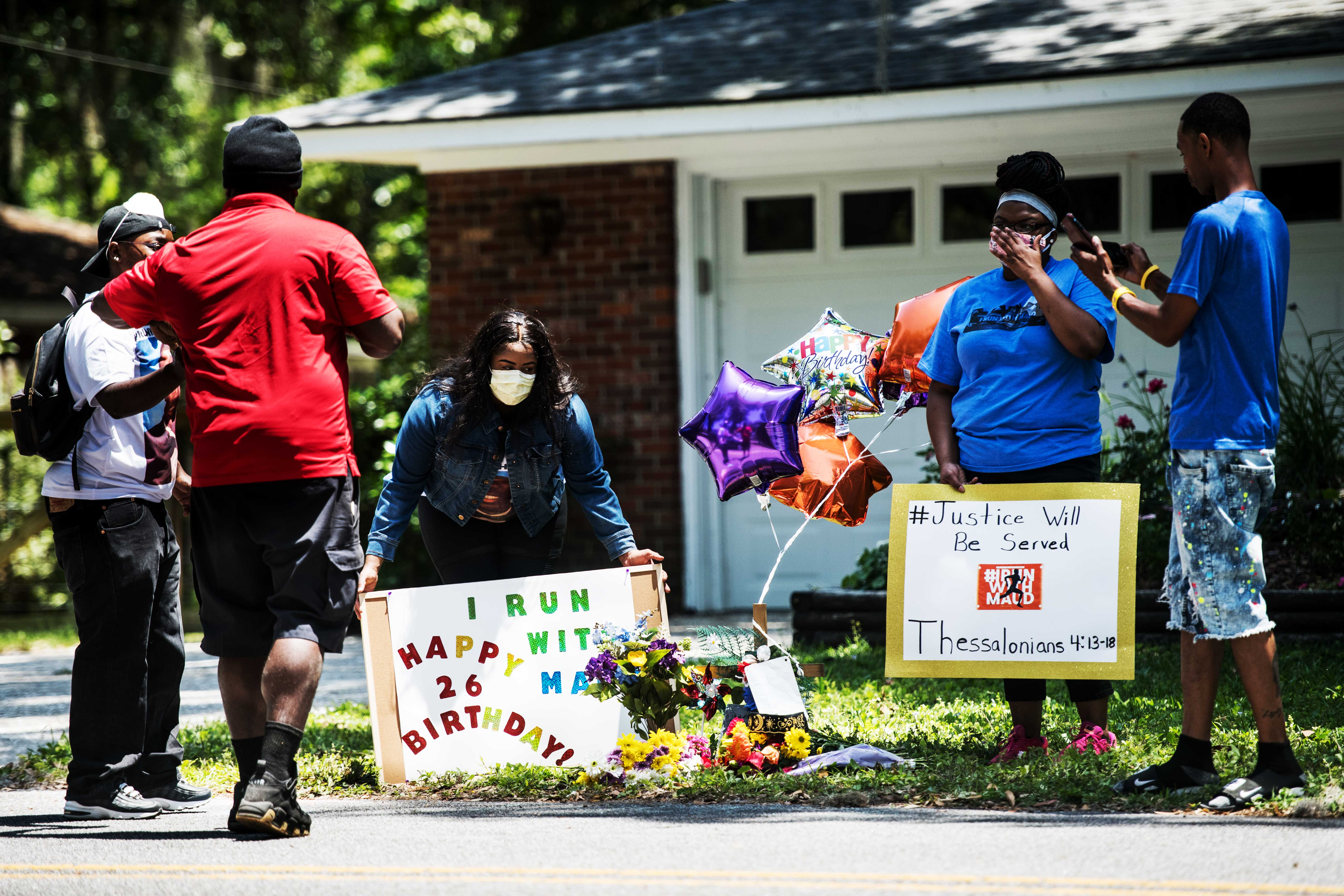 Gathered on the front lawn, standing on the grass with balloons and flowers, a group of black demonstrators hold signs at a memorial for Ahmaud Arbery near where he was shot and killed in Brunswick, Georgia, on May 8.