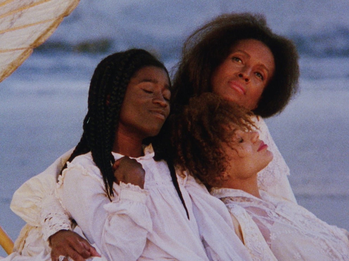 Three Gullah women sit together.