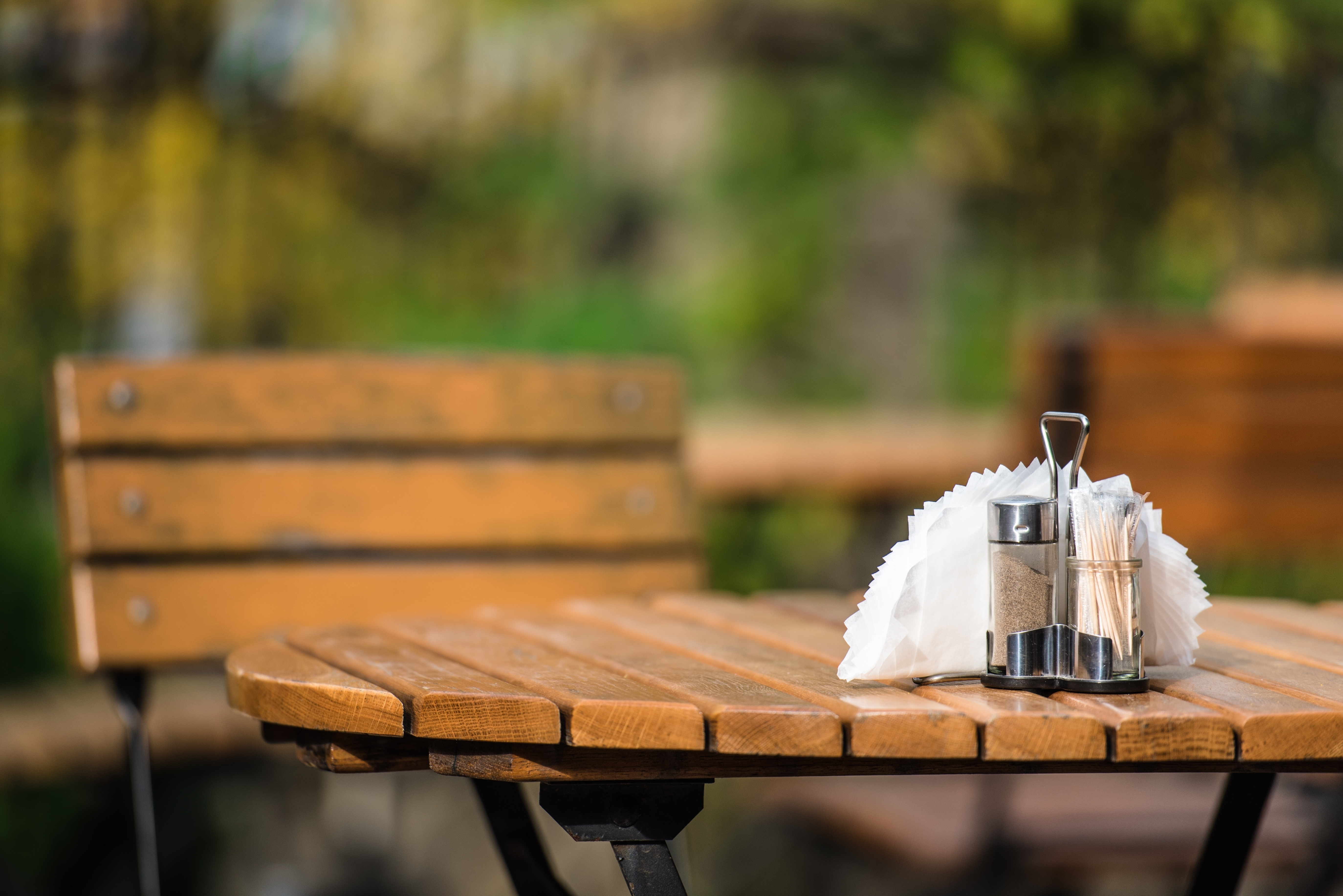 An empty table in an outdoor plaza, with the background blurred and salt and pepper shakers in the foreground