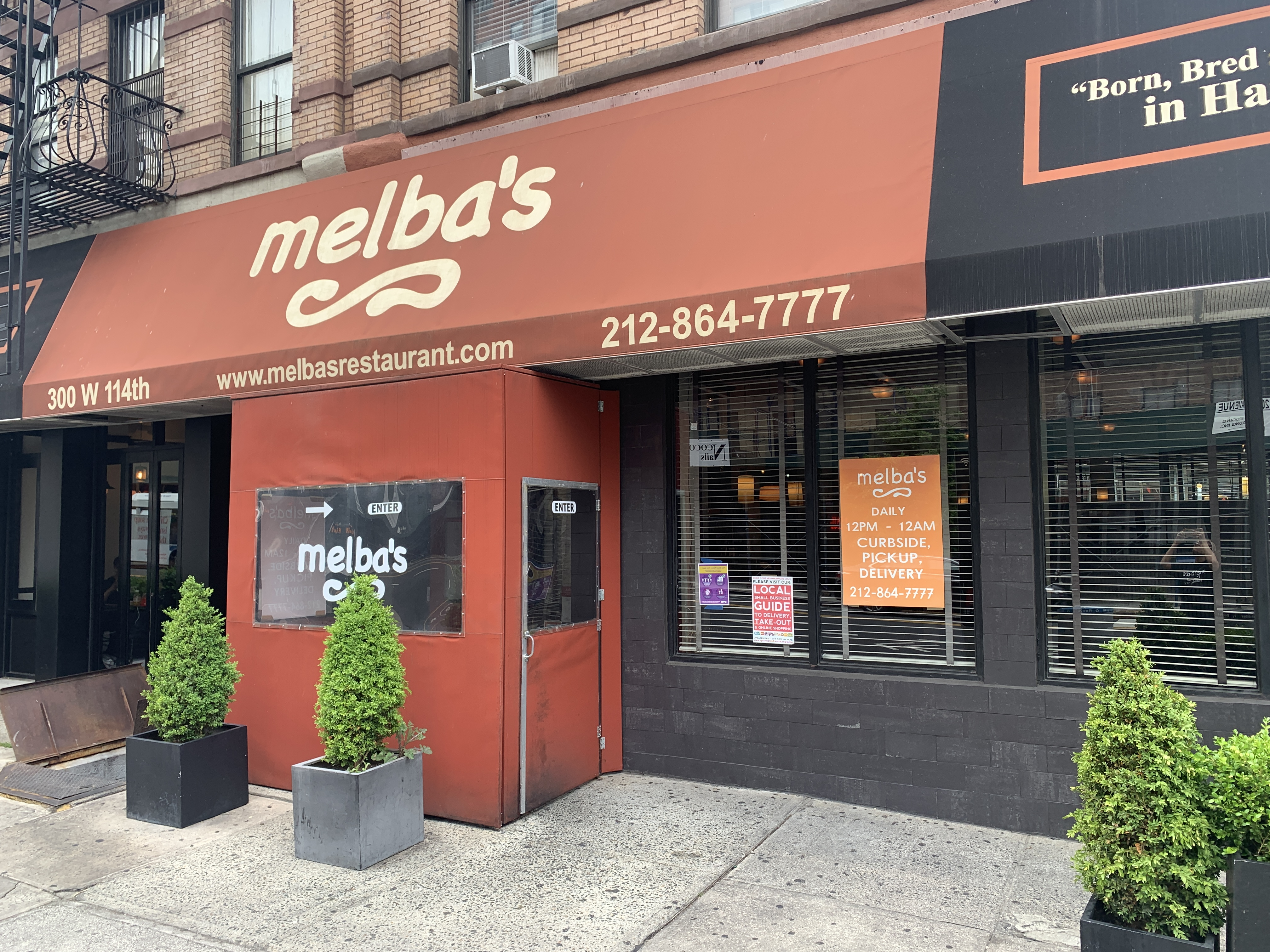 The exterior of the restaurant Melba's in Harlem which has a red awning in the front