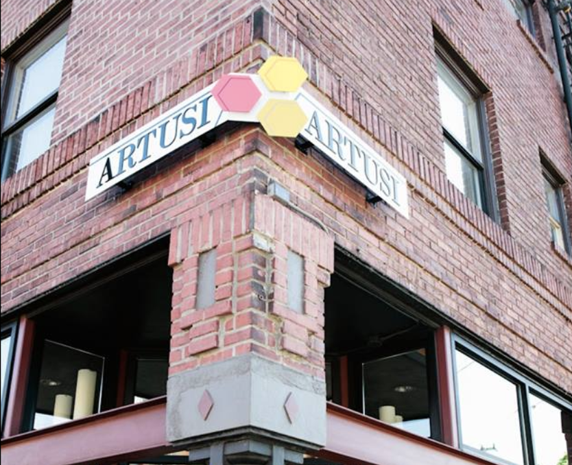 The front of Artusi in Capitol Hill, a brick building with signage wrapping its corner