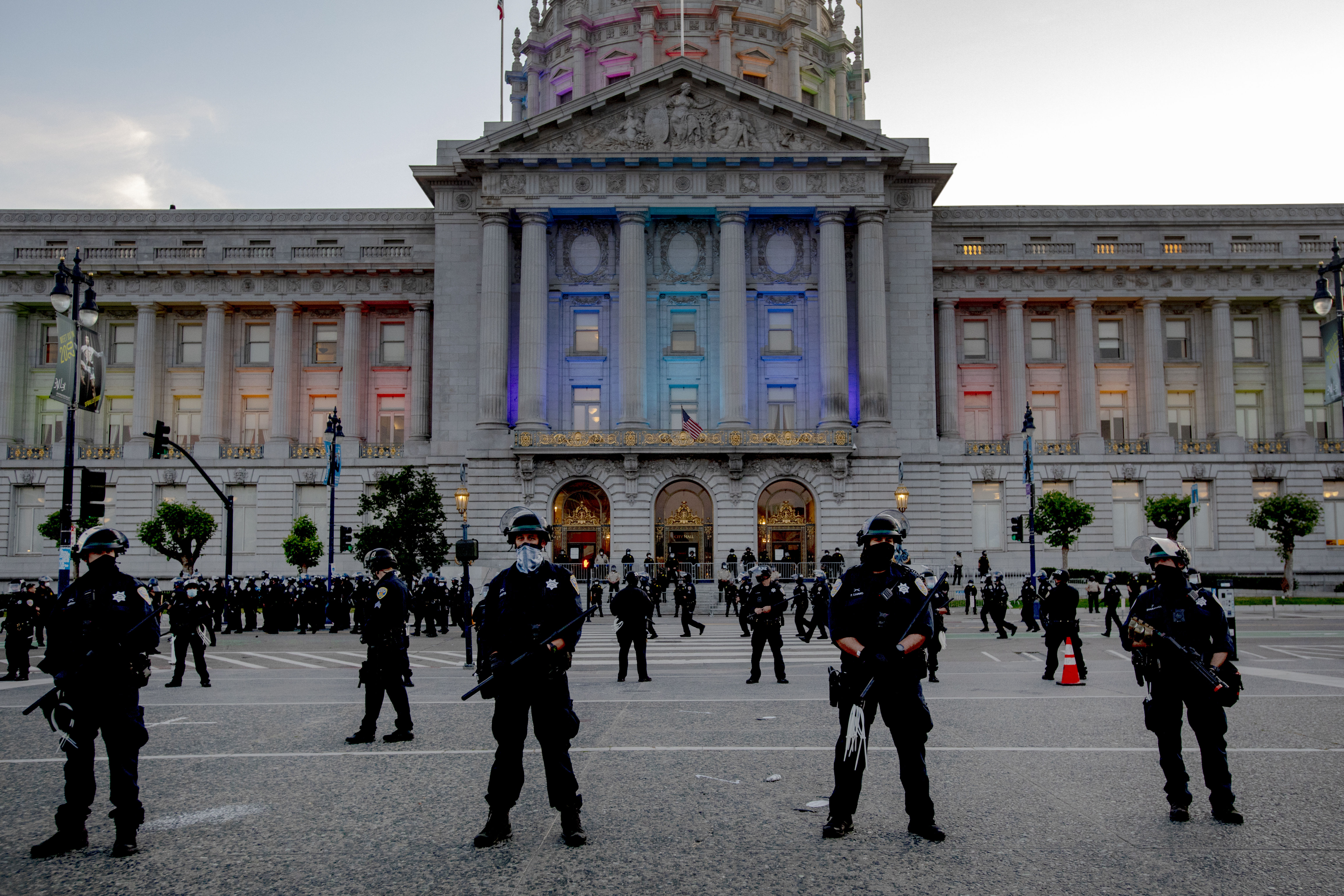 Rows of police officers stand in front of a large building.