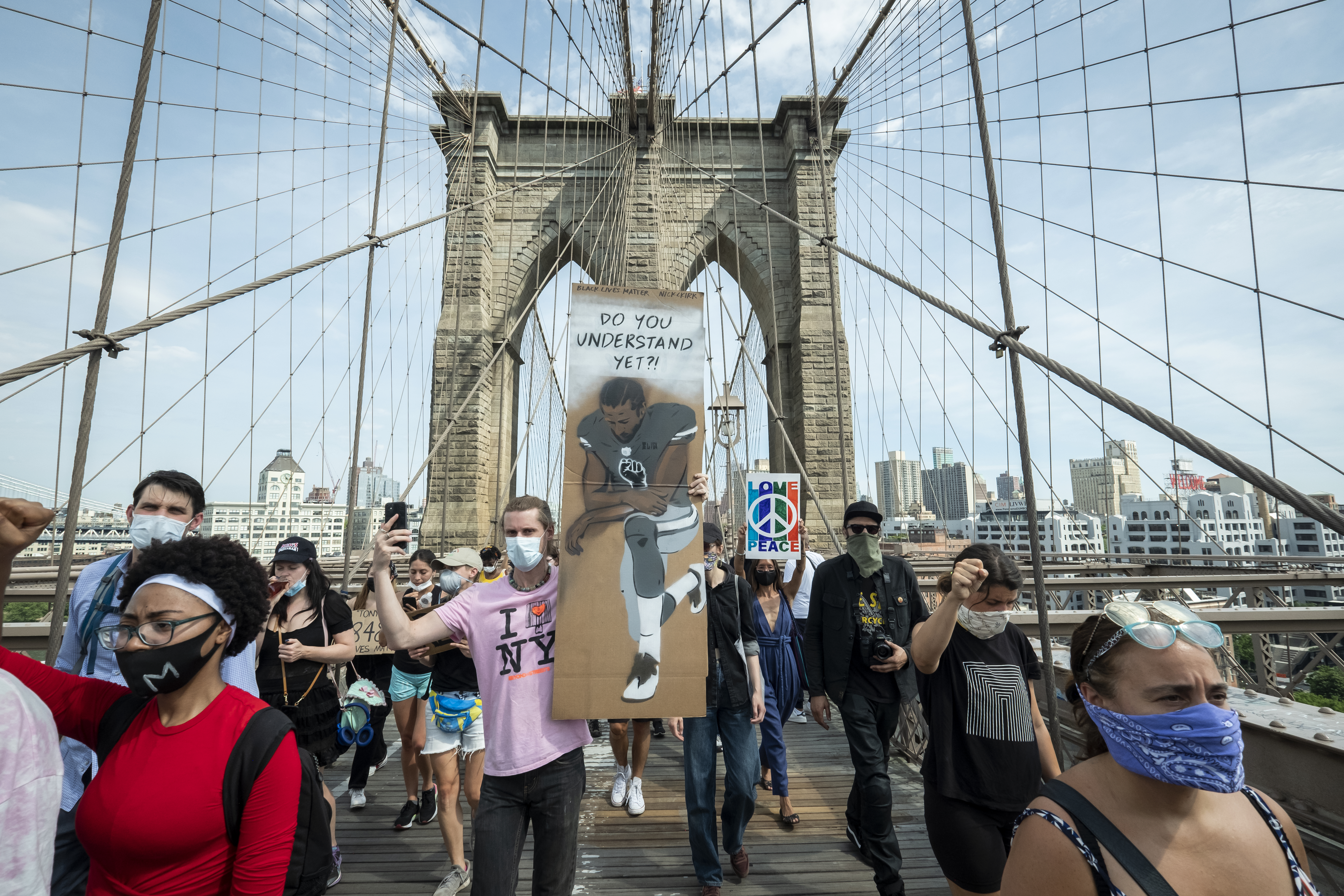 "A protester on the Brooklyn Bridge holds a sign that says, ""Do You Understand Yet?"" with a picture of Colin Kaepernick taking a knee. June 04, 2020."
