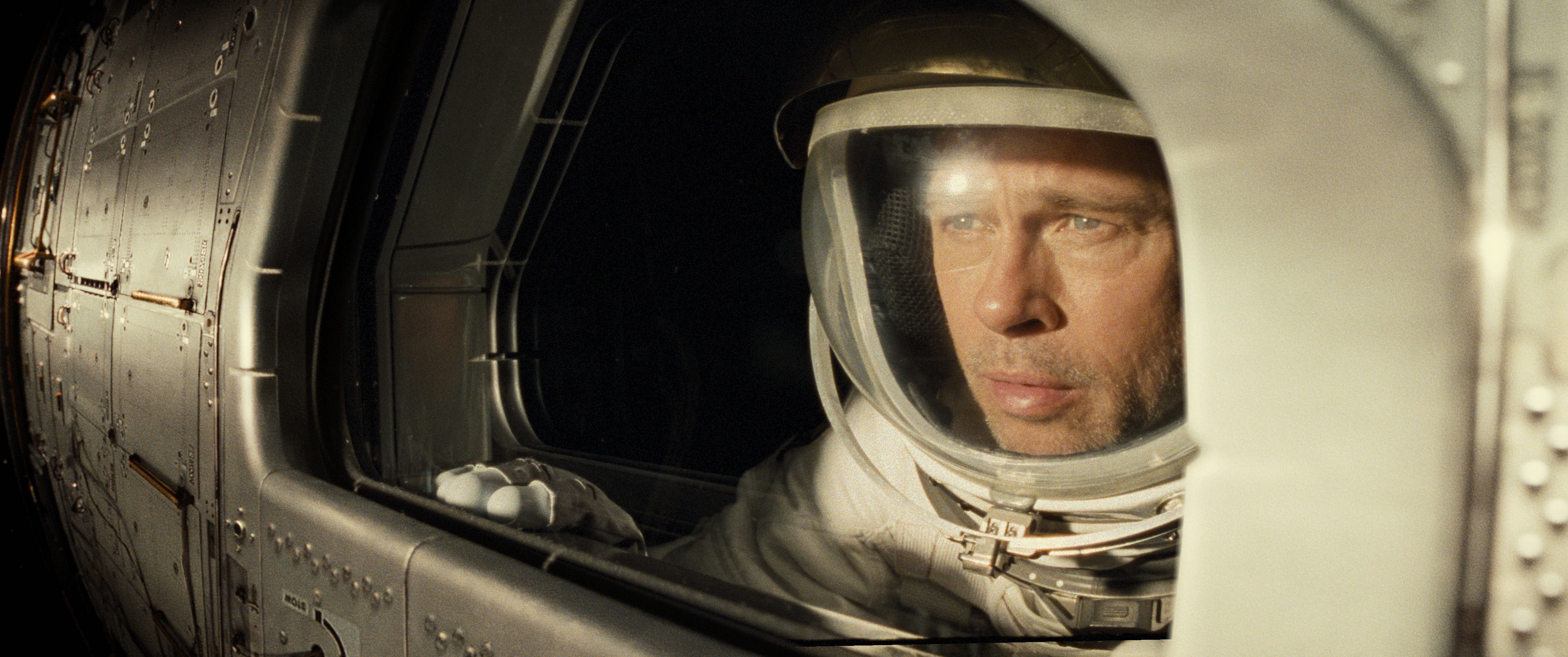 brad pitt's roy wears a space suit and watches out a window as his shuttle passes the sun in Ad Astra