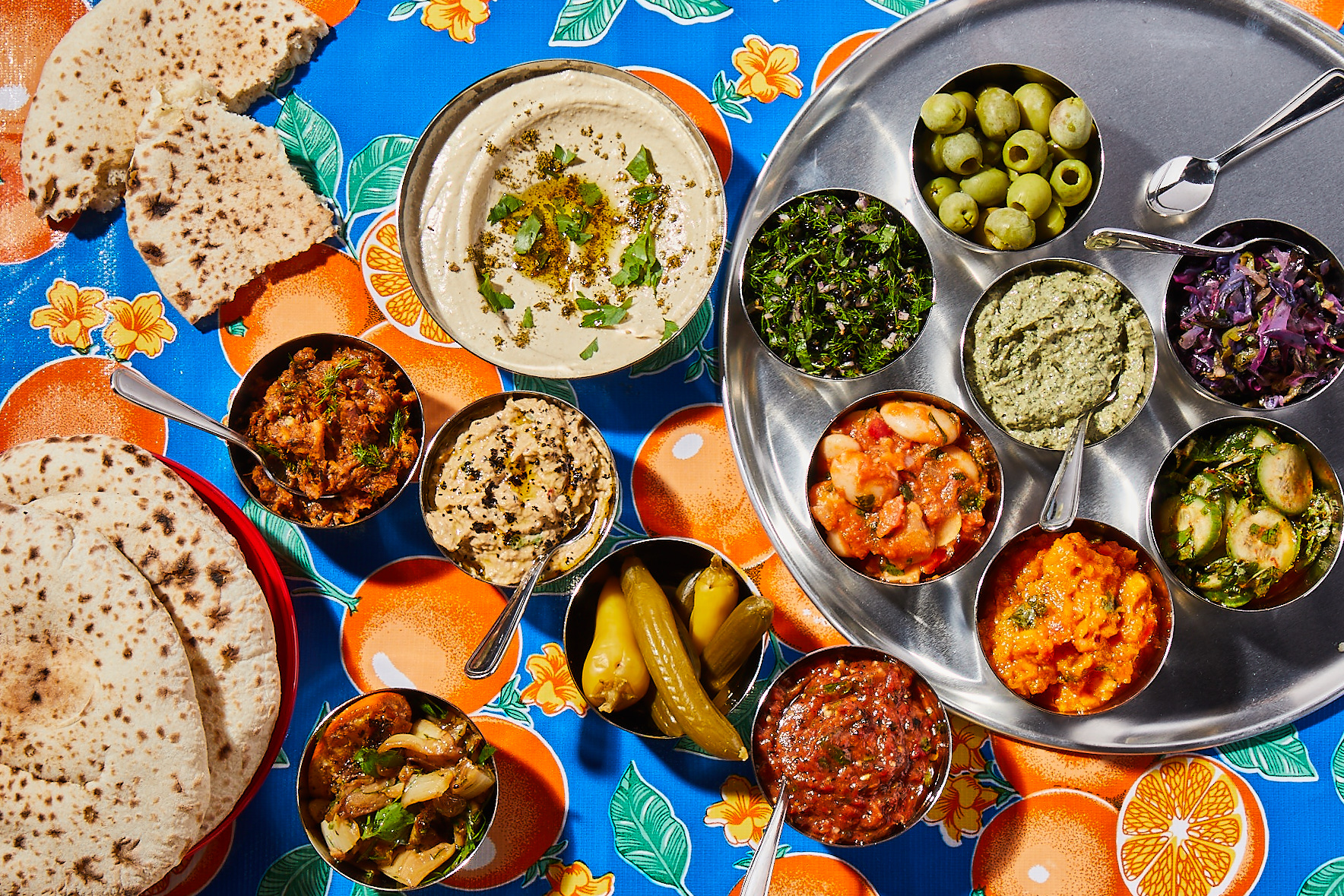brightly colored tablecloth covered with small vegetable dishes