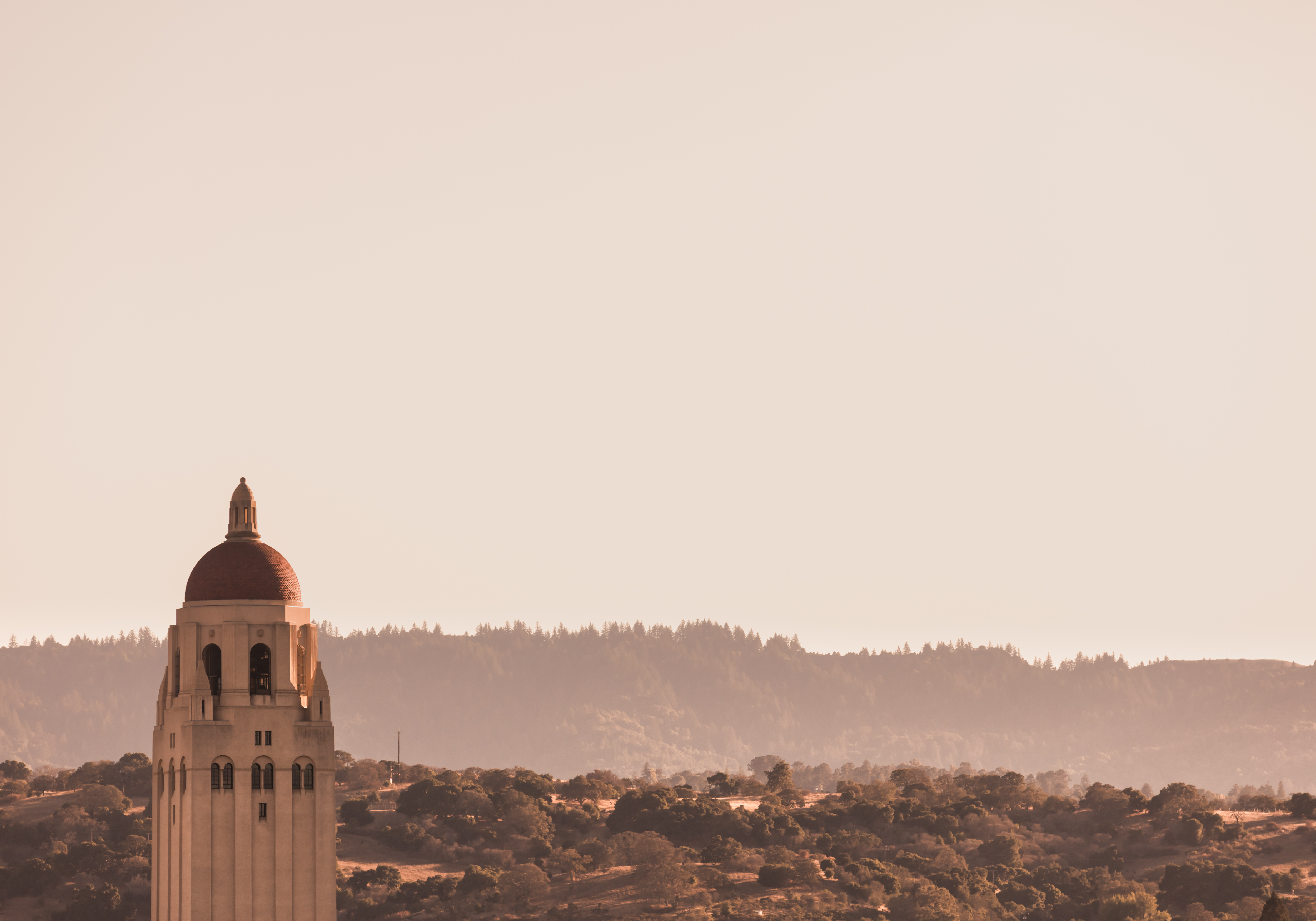 The Hoover Tower of Stanford University is seen with hills behind it.