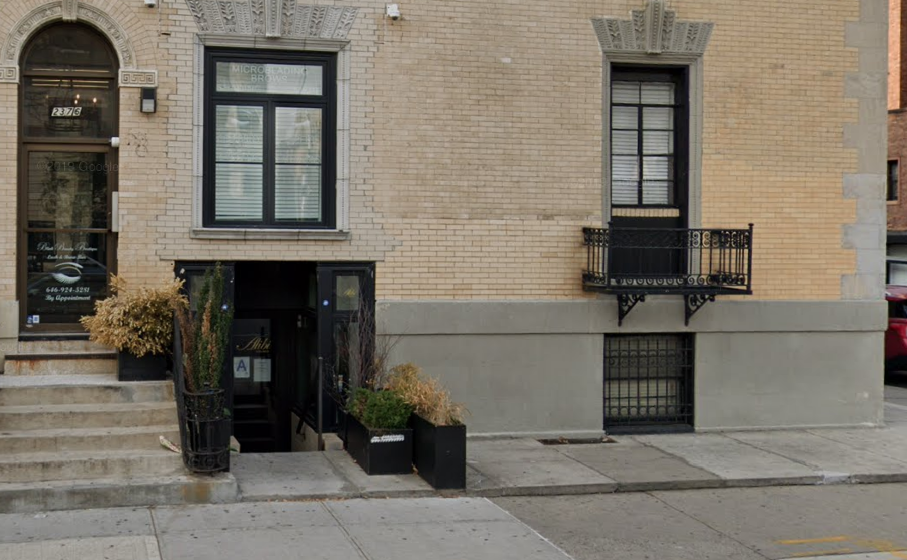 The exterior of an underground bar in Harlem with a yellow brick exterior and a black paneled door
