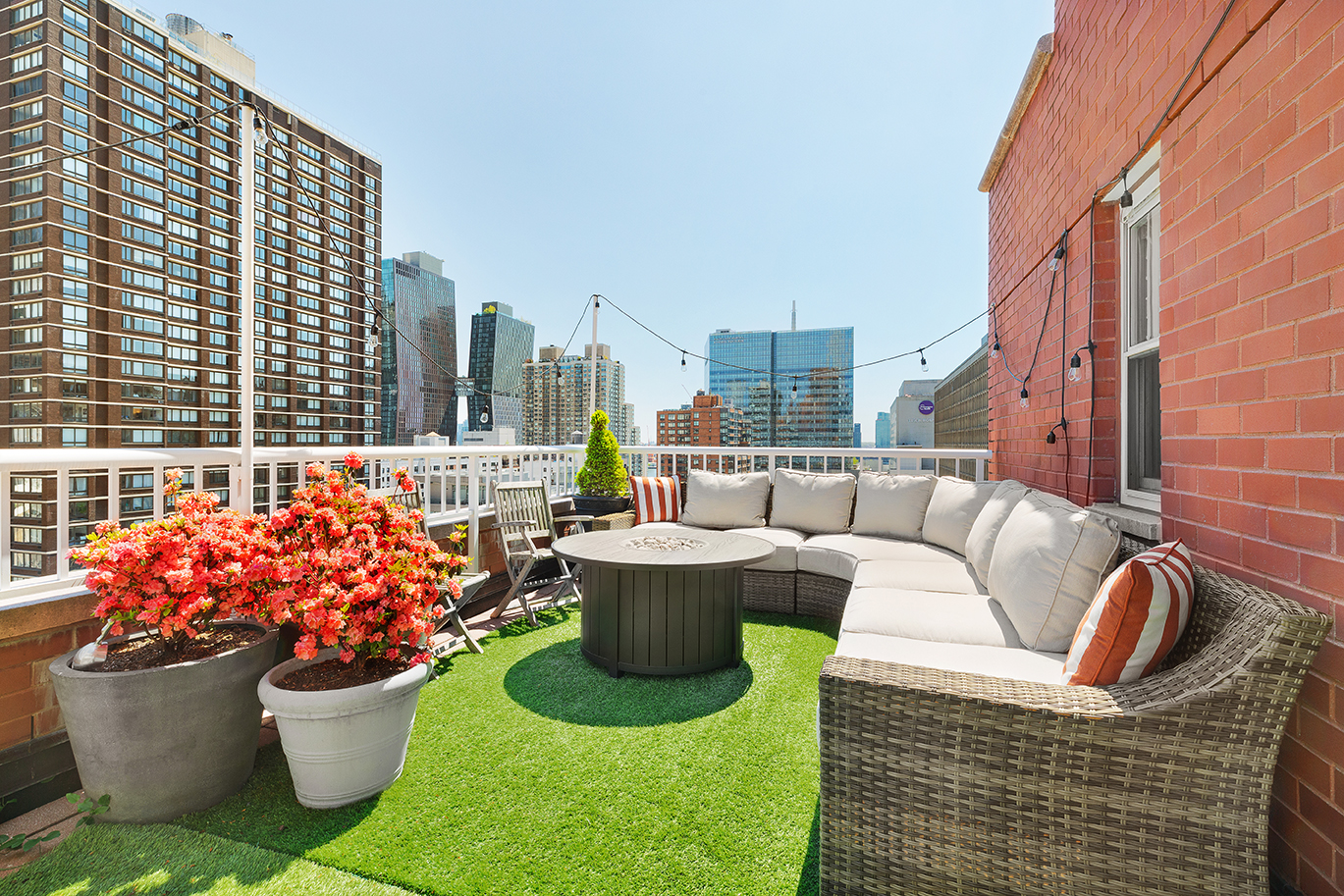 A terrace with a large beige couch, several planters, and a round wooden table.