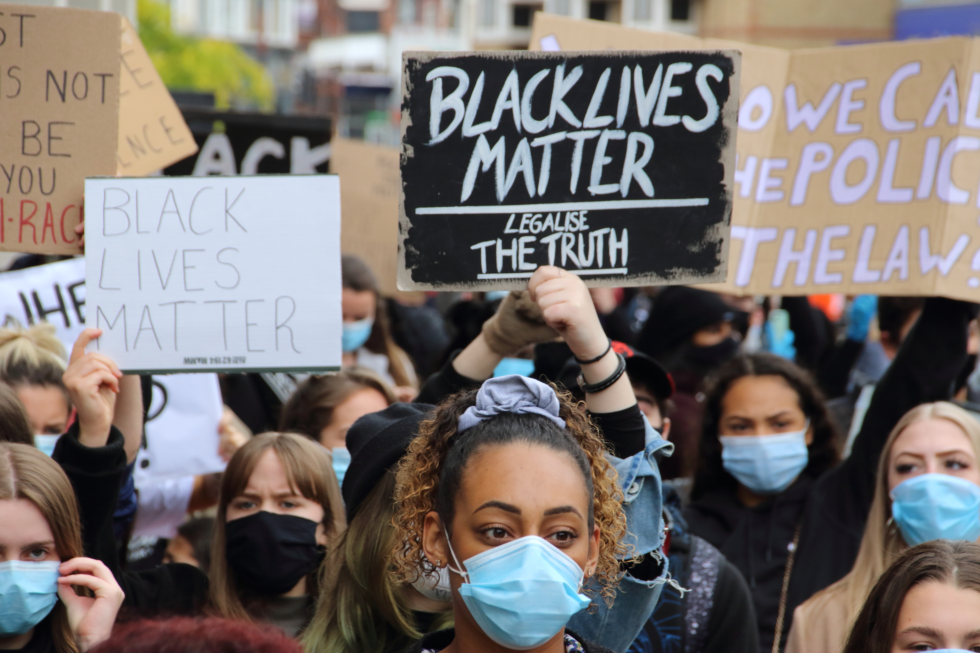 Protesters wearing protective masks hold BLM placards during...