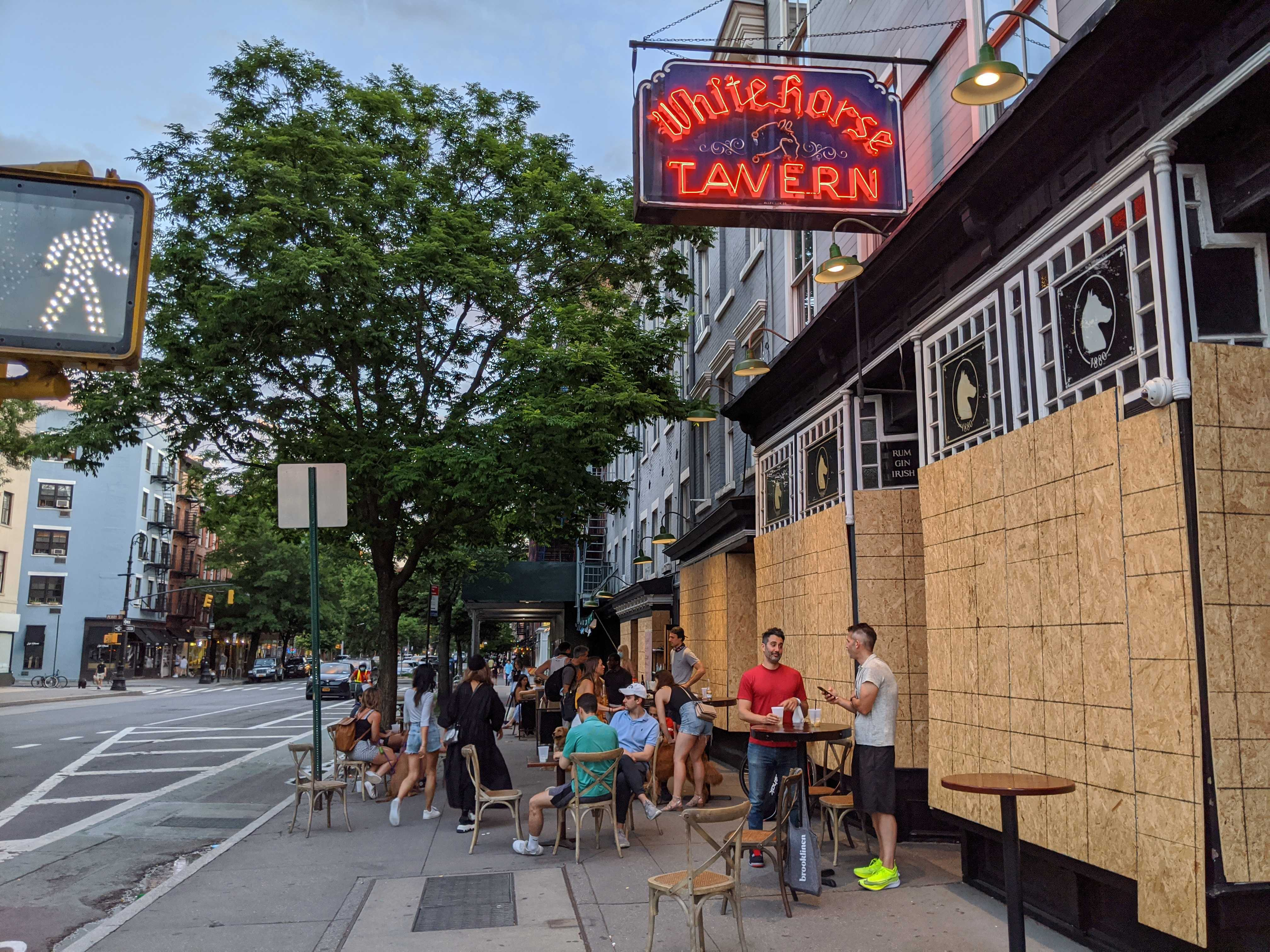 A boarded up restaurant with tables and chairs set up outside on the sidewalk and customers sitting and drinking in front of the restaurant.
