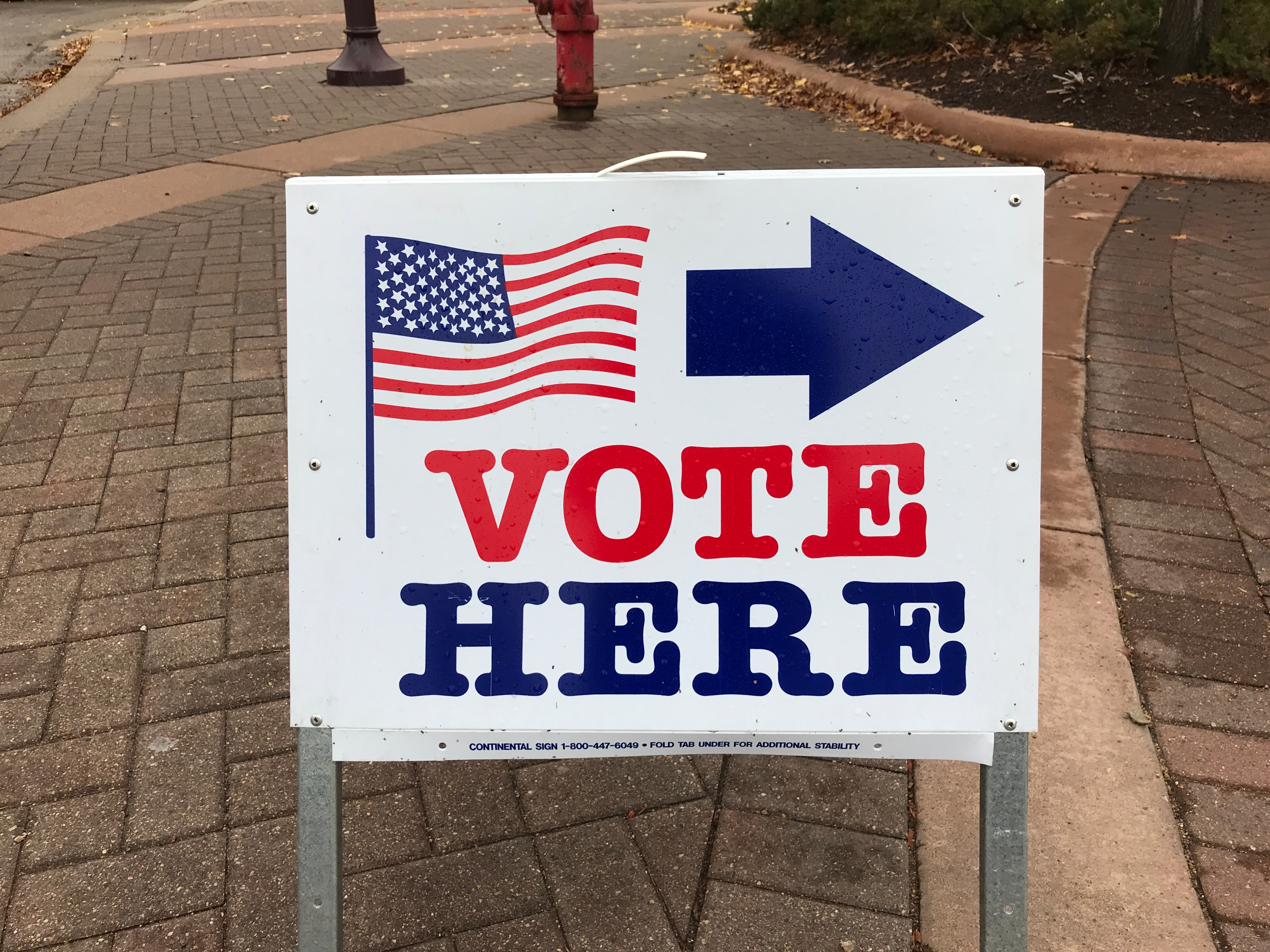 """A sign that reads """"vote here"""" on a cobblestone sidewalk in Minnesota."""