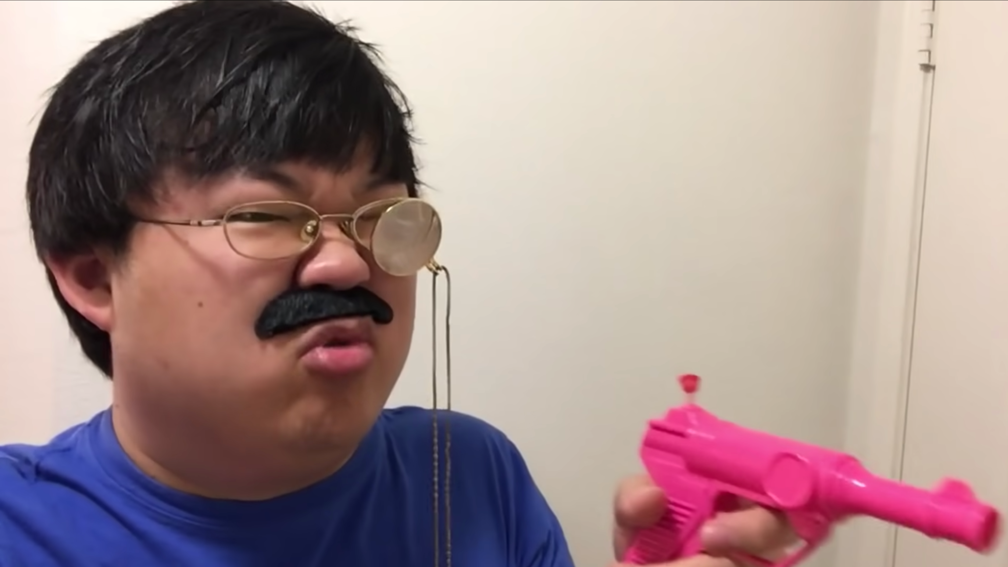 A screencap of SungWon Cho brandishing a pink water pistol while wearing a fake mustache and a monocle over his glasses.