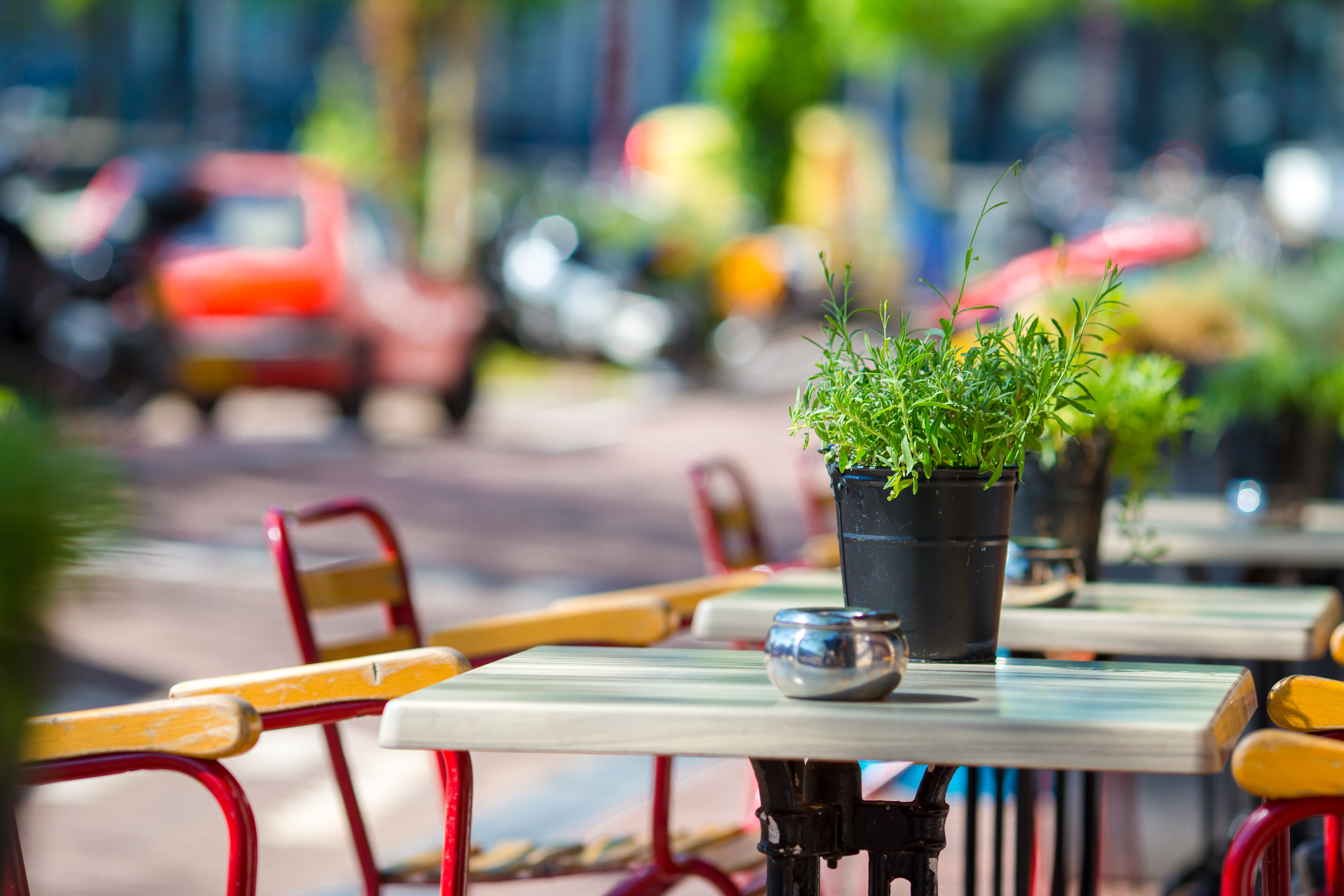 Empty outdoor tables with plants on top and red chairs