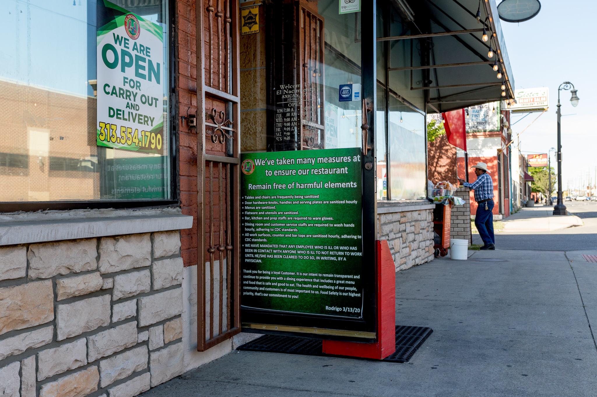 A green sign on the open door to El Nacimiento in Detroit.