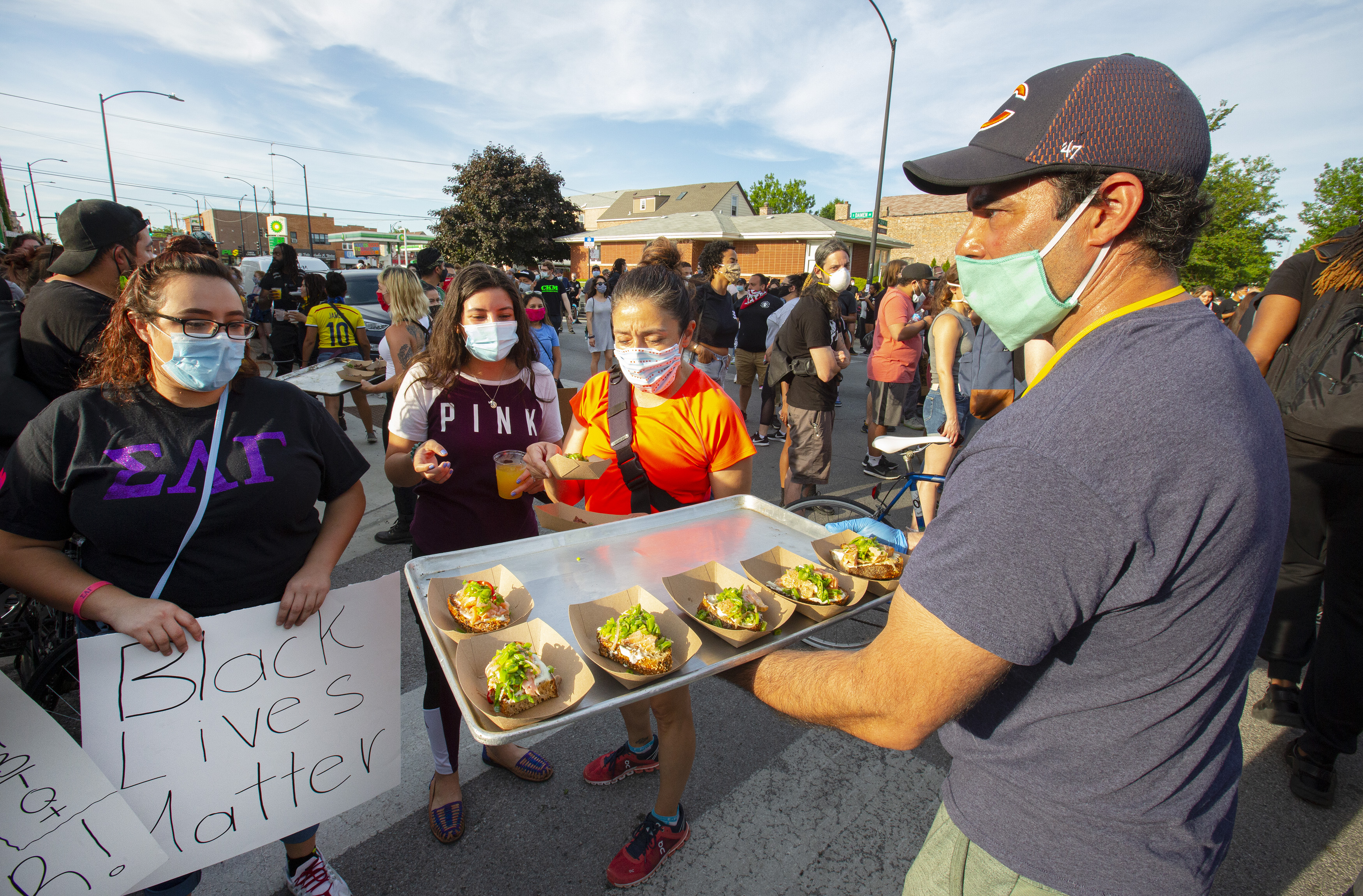 """Two women stand wearing masks looking a man in a mask. He is holding a tray of tacos. One of the women carries a sign that says """"Black Lives Matter."""""""