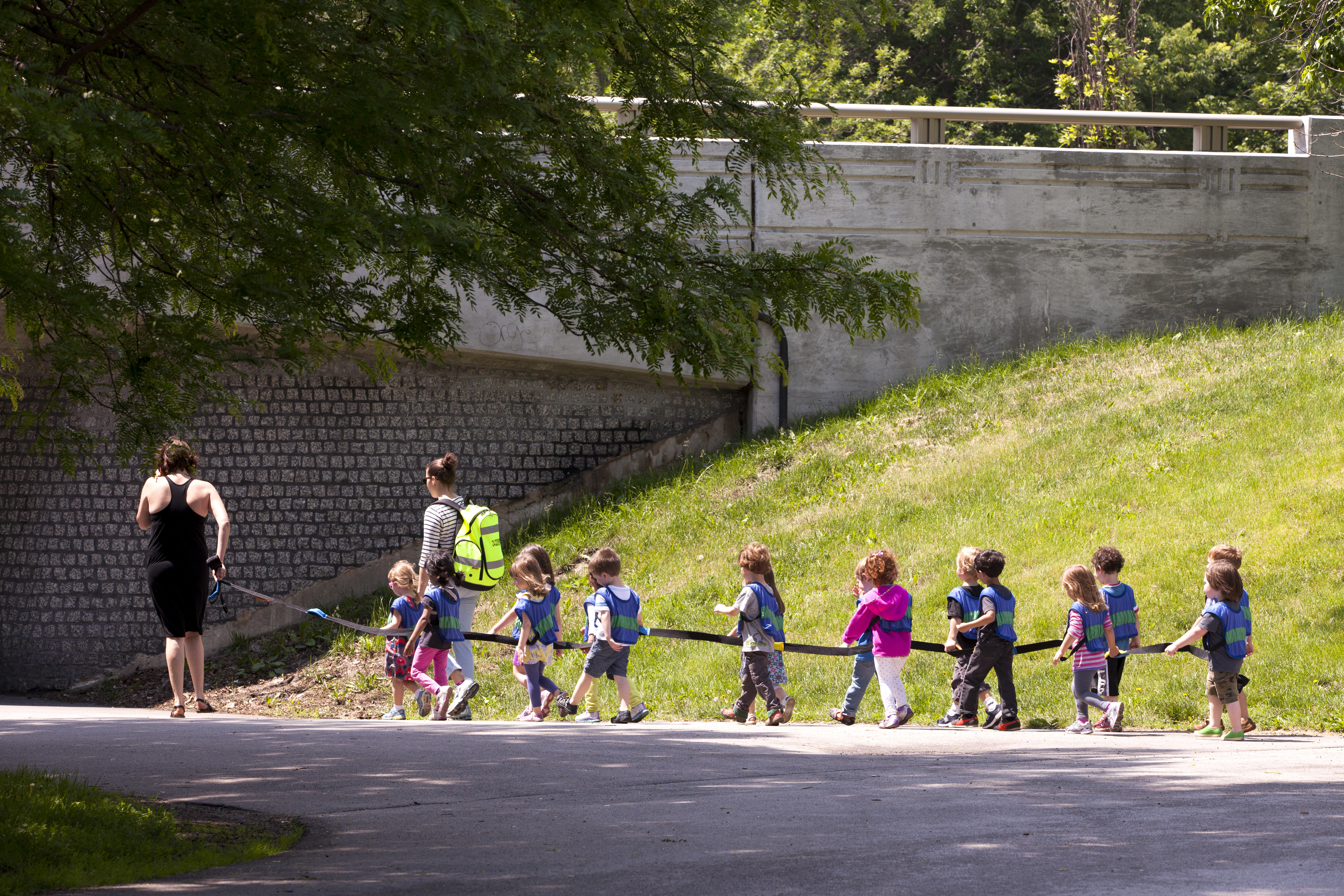 Daycare children on a long leash and their caretakers enjoy a walk through a Chicago park