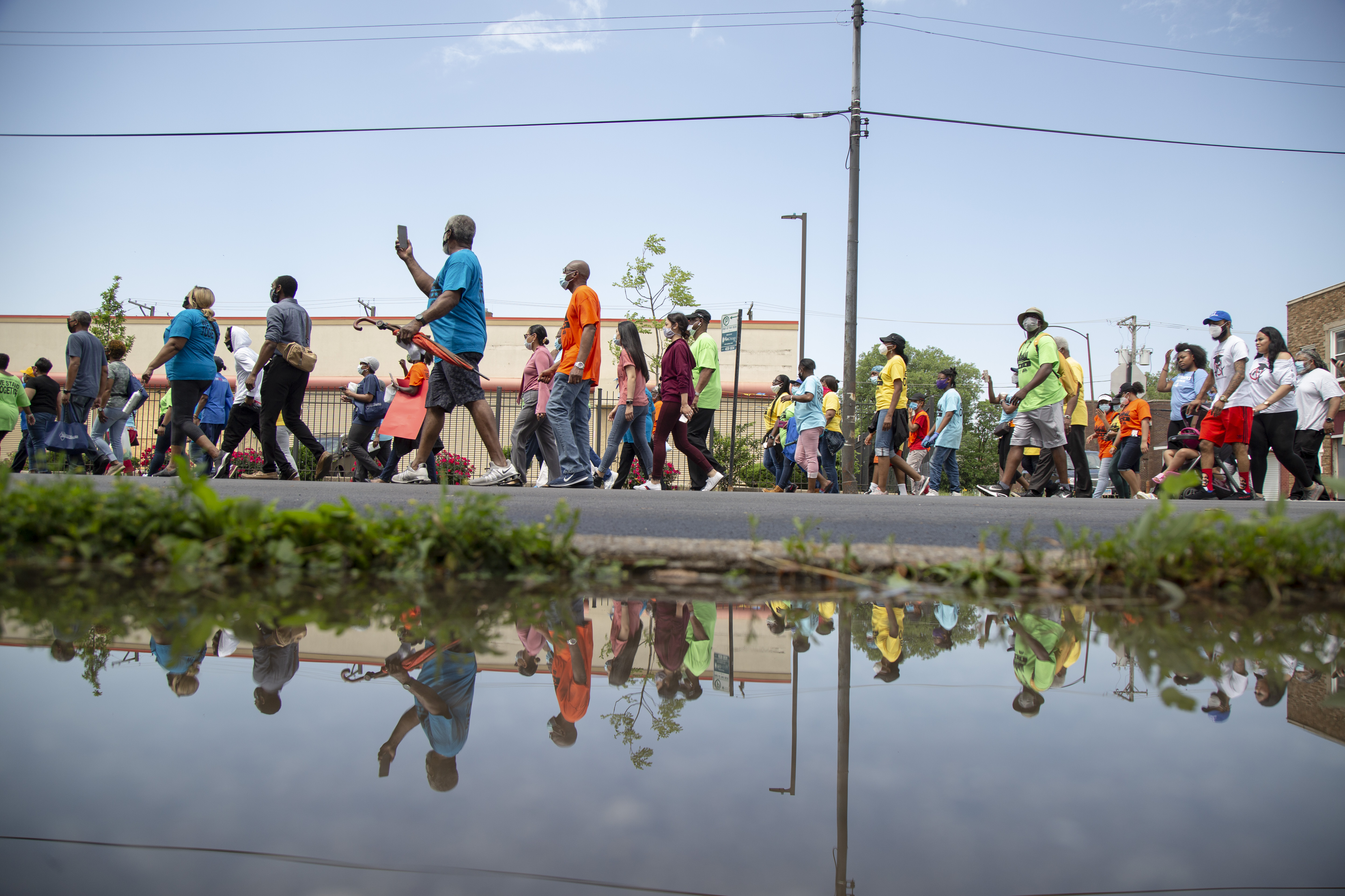 Community members walk down the street during a march in Roseland, Wednesday June 10, 2020. The group marched to unite the community toward progress and sustainability after some businesses along South Michigan Avenue were damaged.