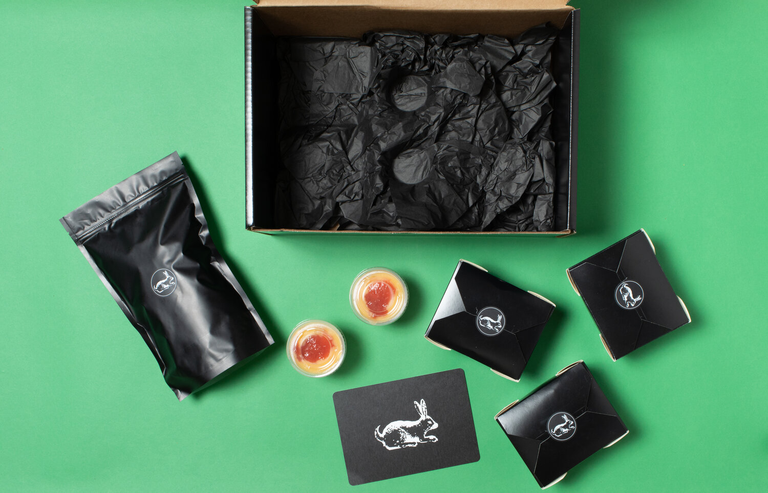 A top-down image of the boxes part of Tarsan i Jane's paella kit, with a green background