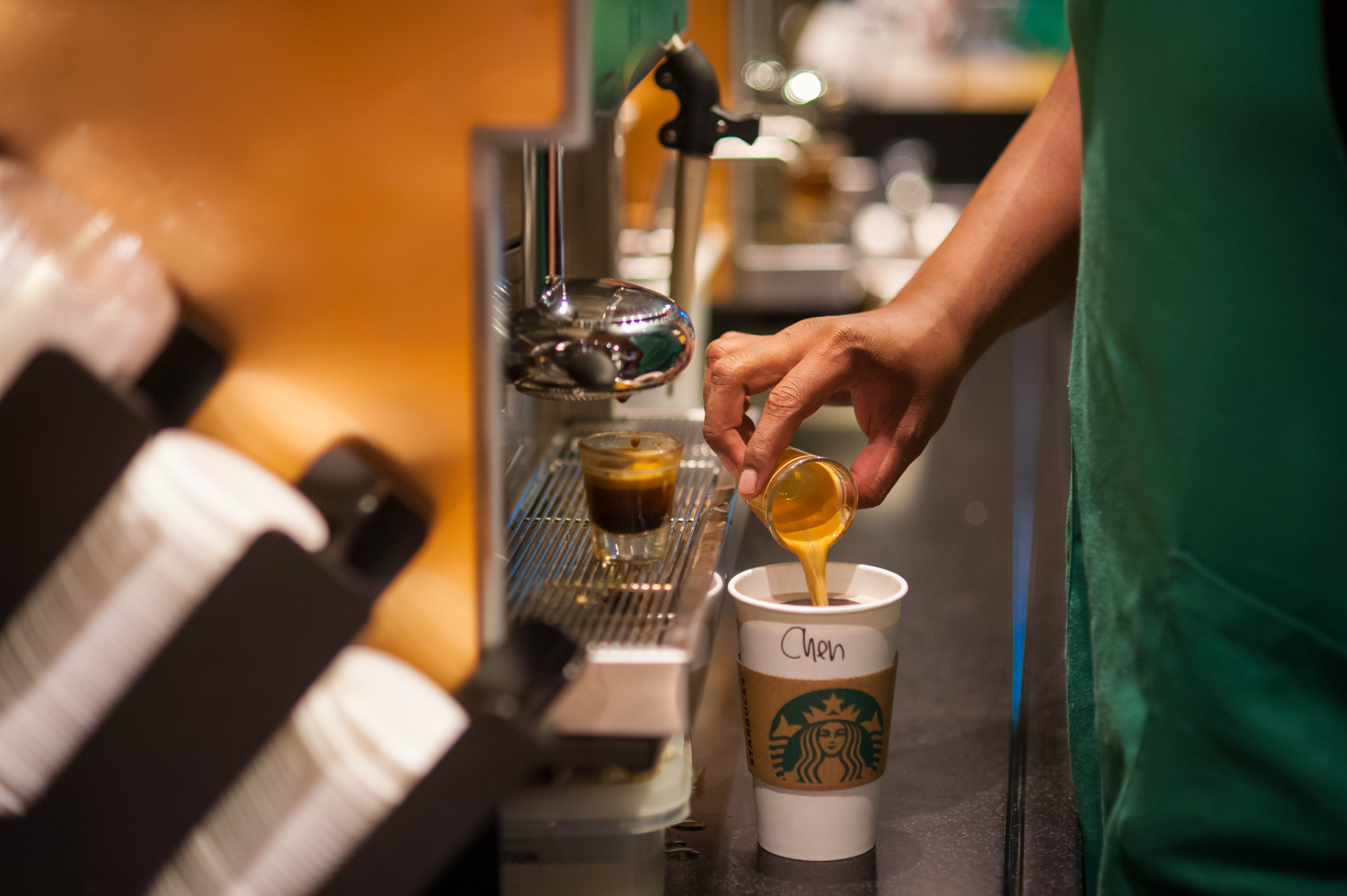 A closeup of a Starbucks employee's hand pouring espresso into a paper to-go cup with Starbucks branding.