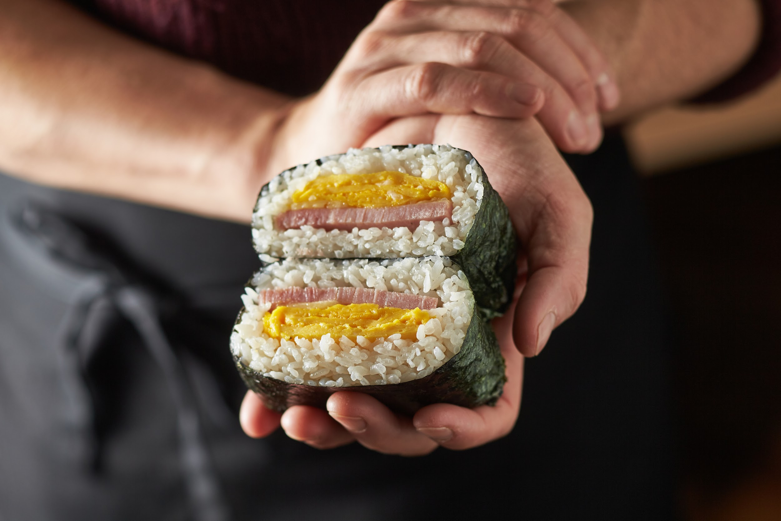 A hand holds a seaweed-wrapped ball of rice filled with ham and egg