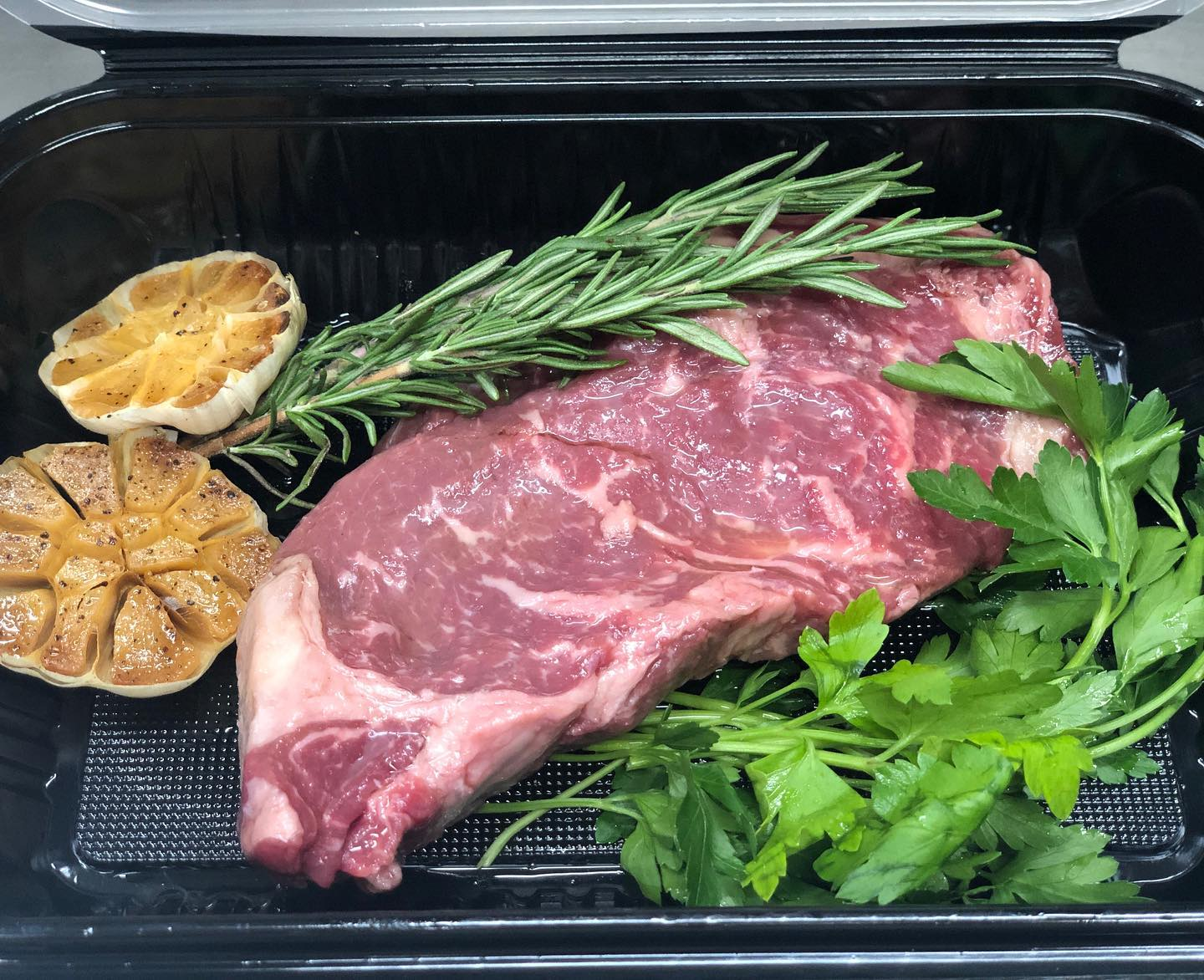 a raw steak surrounded by garlic cloves and rosemary