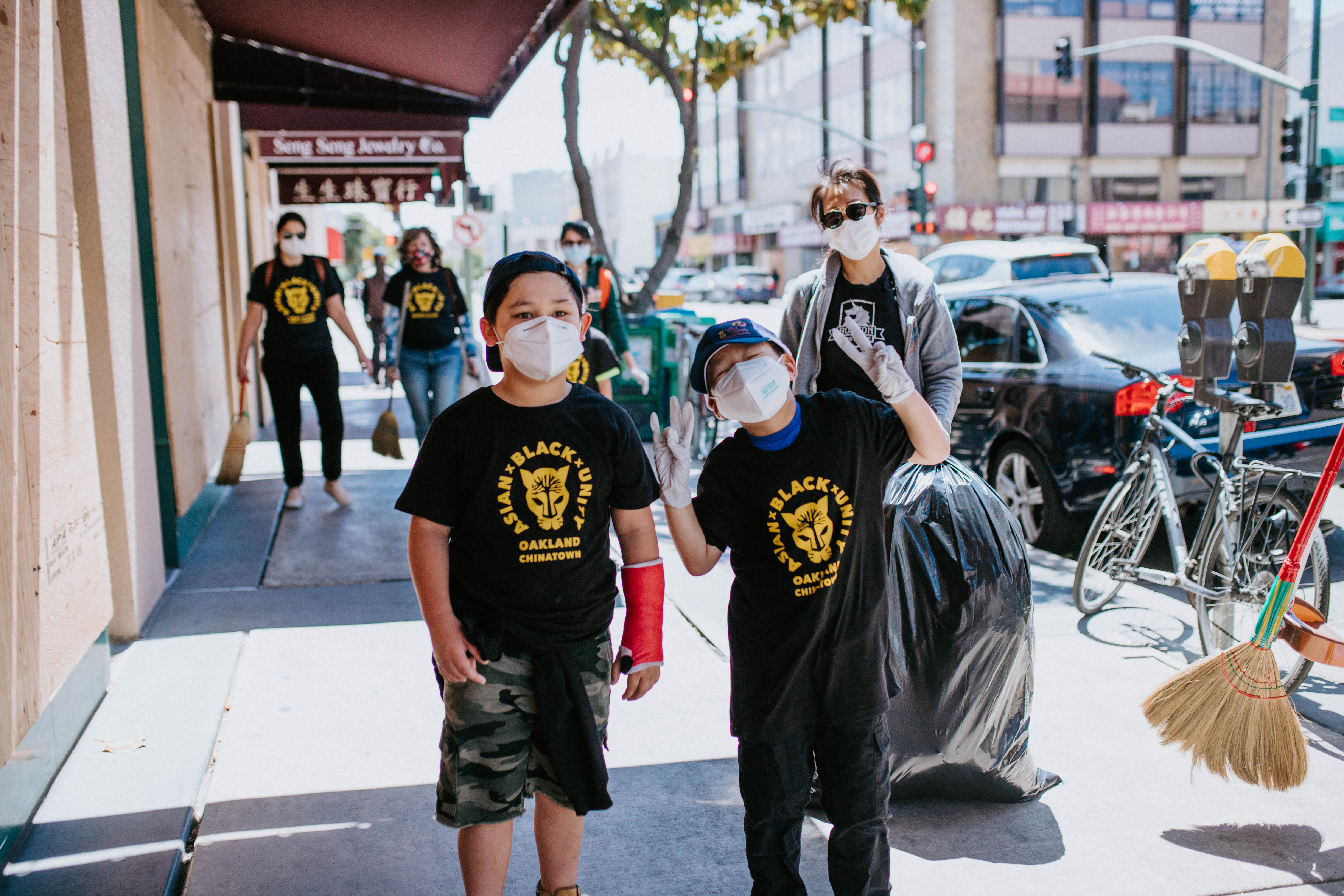 """Two children wearing """"Asian x Black x Unity"""" T-shirts at a Chinatown cleanup event on Sunday, June 7"""