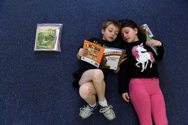 Van Current, 6, left, and Natasha Williams, 7, read quietly together at Denver Green School.