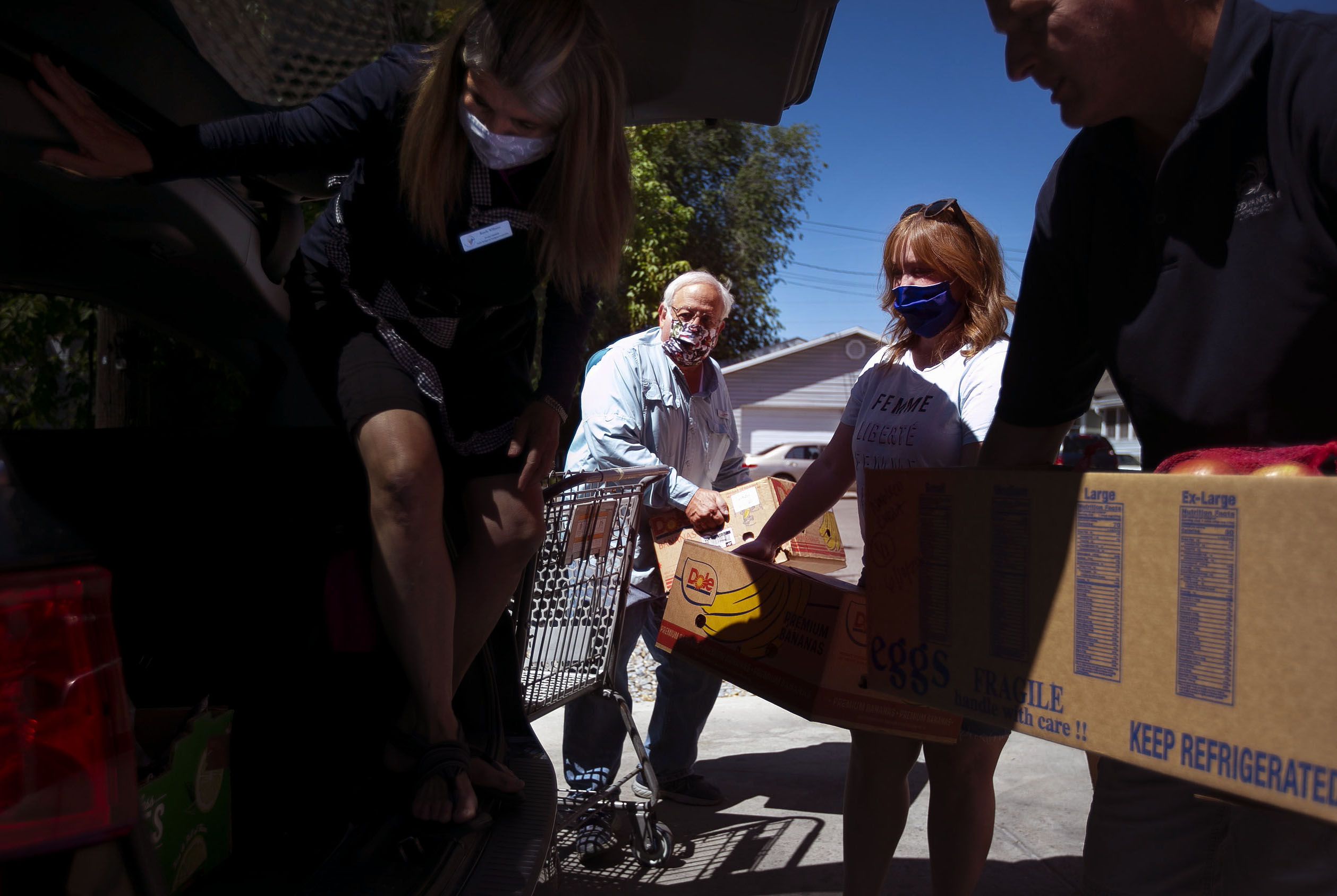Randy Williams, a member of the Cache Refugee & Immigrant Connection board, left, volunteer Bruce Haslem, Jess Lucero, another board member, and Matt Whitaker, director of the Cache Community Food Pantry, load a car with food donations at the pantry in Logan on Thursday, June 11, 2020. Nonprofits, state and local government and churches have teamed up to assist refugees in northern Utah who work at a meatpacking plant in Hyrum and have tested positive for COVID-19. The recent rise in cases statewide is attributed to the outbreak at JBS Hyrum Beef where many refugees and immigrants work.