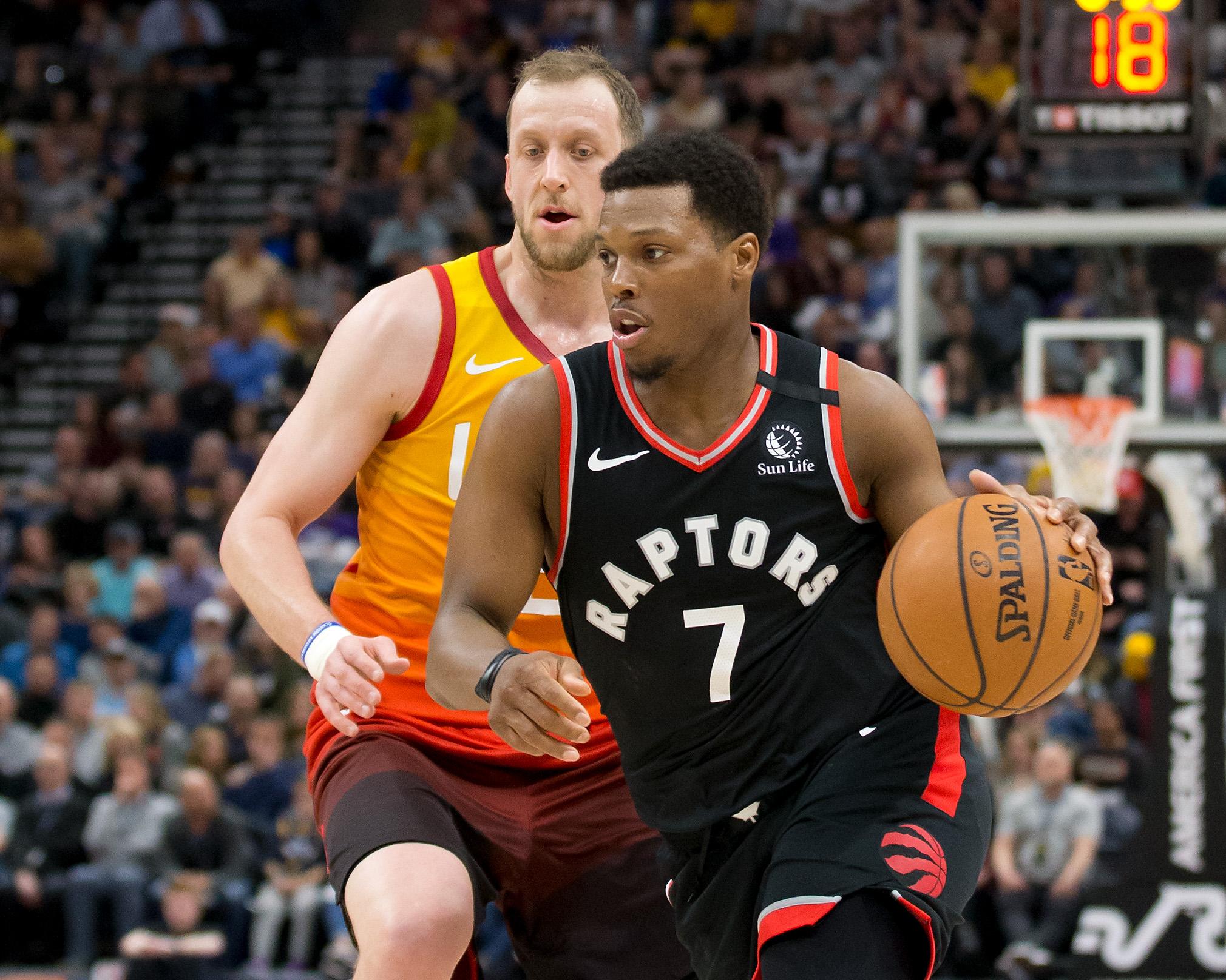 Toronto Raptors guard Kyle Lowry dribbles the ball ahead of Utah Jazz guard Joe Ingles during the first half at Vivint Smart Home Arena.