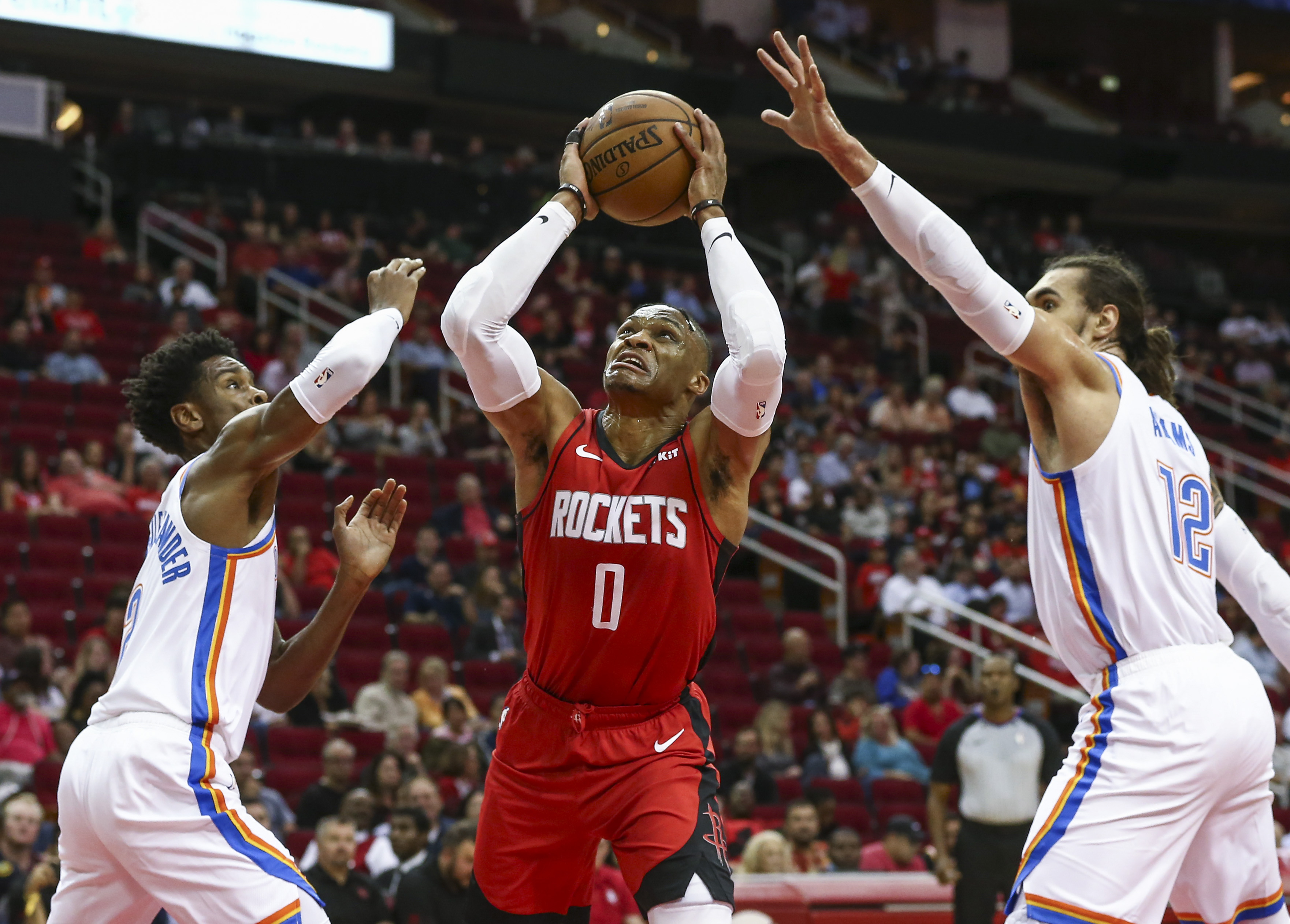 Houston Rockets guard Russell Westbrook attempts to score a basket as Oklahoma City Thunder guard Shai Gilgeous-Alexander and center Steven Adams defend during the first quarter at Toyota Center.