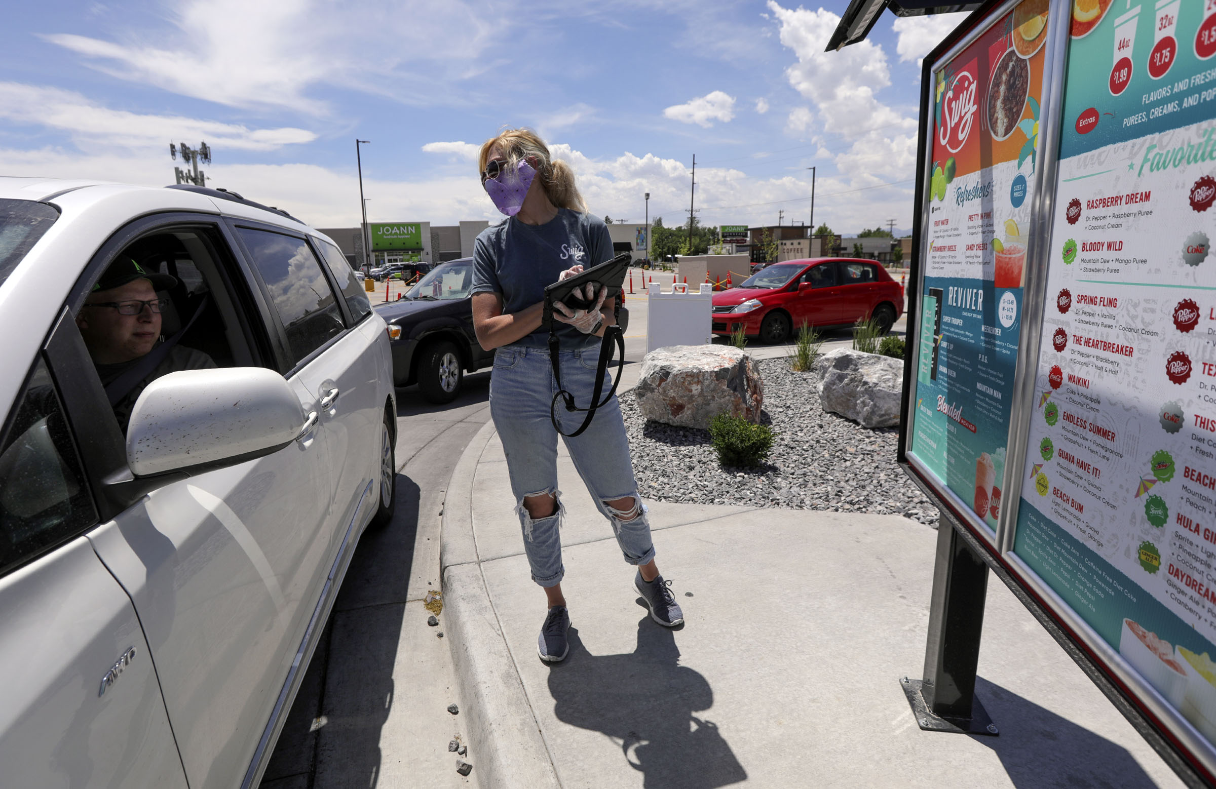 Jennifer Huntington, general manager of Swig's in Millcreek, takes an order from Tyson Taylor in the drive-thru lane on Wednesday, June 3, 2020.