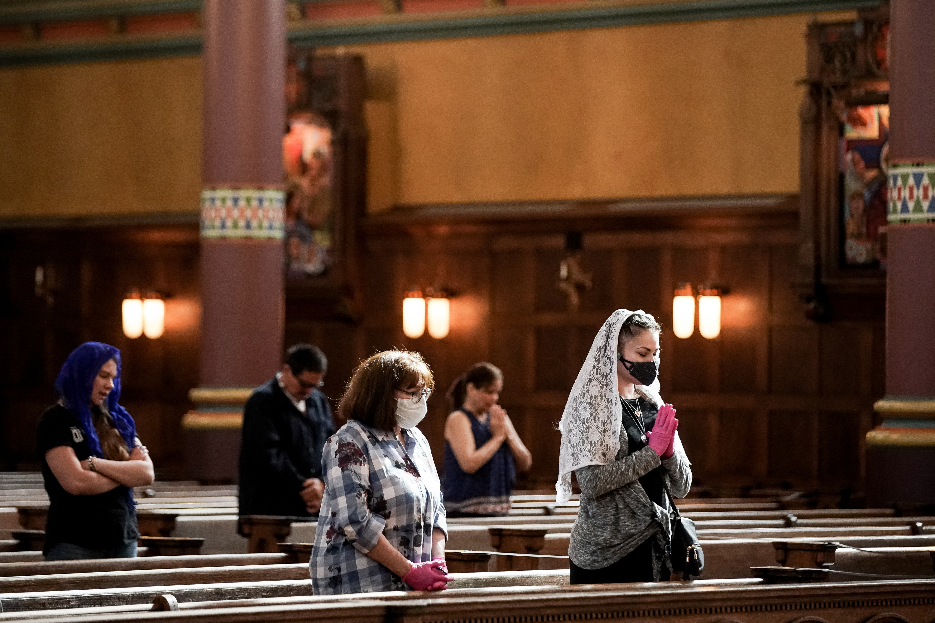 Ursula Quintana, right, and her mother, Joleen Rogers, third from left, attend Mass at the Cathedral of the Madeleine on Tuesday, May 12, 2020.