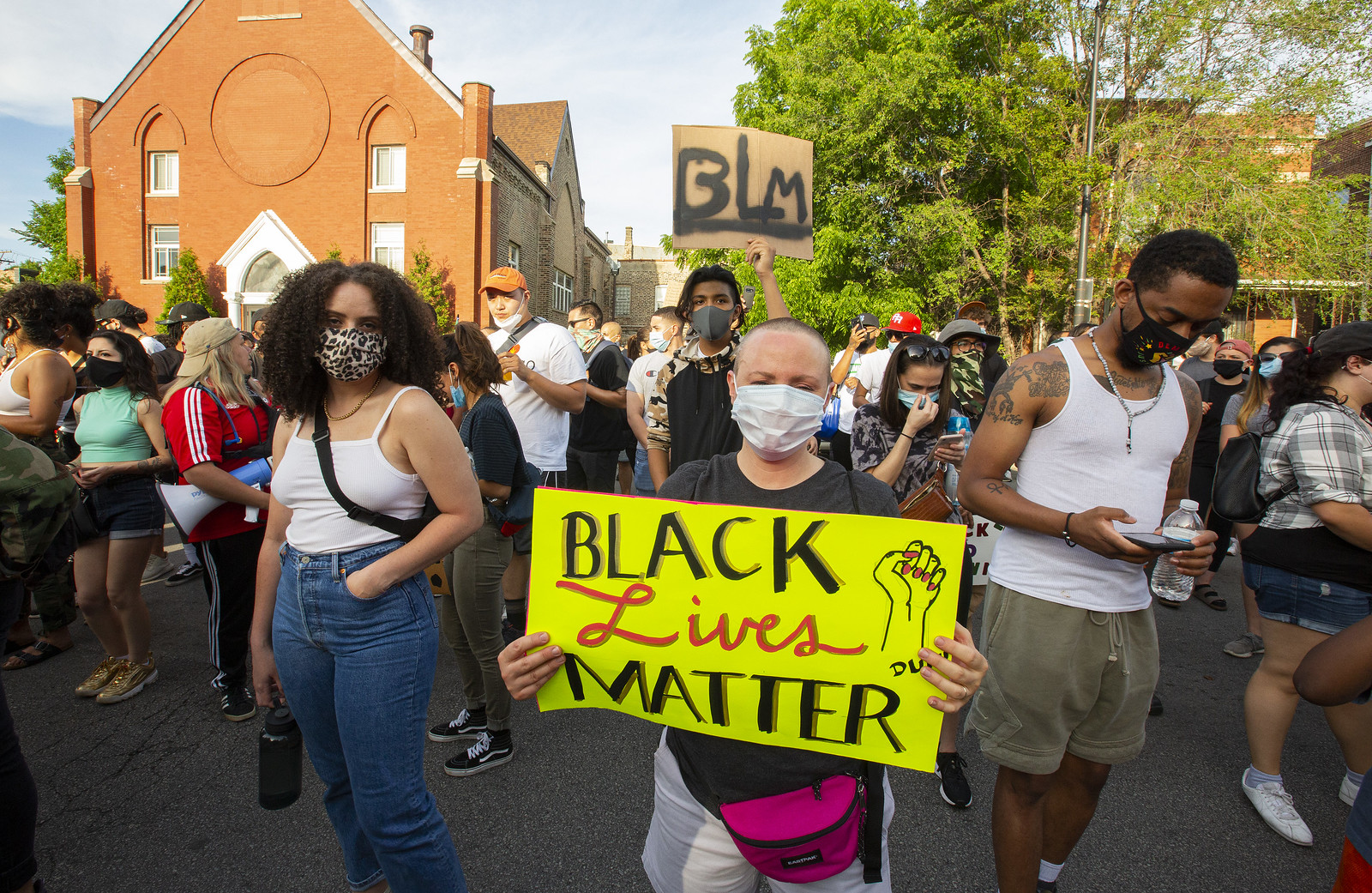 """A masked person holds a """"Black Lives Matter"""" sign in a crowd."""