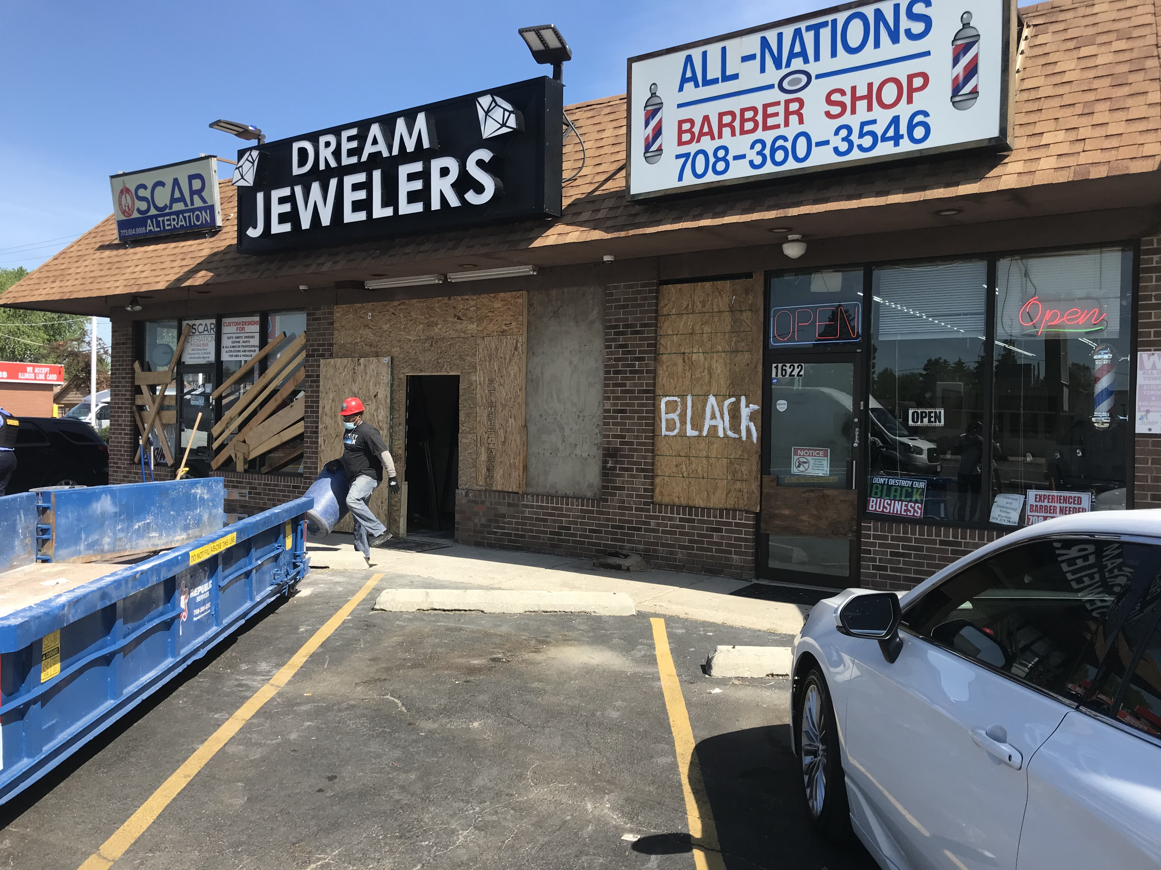 A Cook County sheriff's employee throws away trash outside of Dream Jeweler in Calumet City. The business was recently damaged by looters.