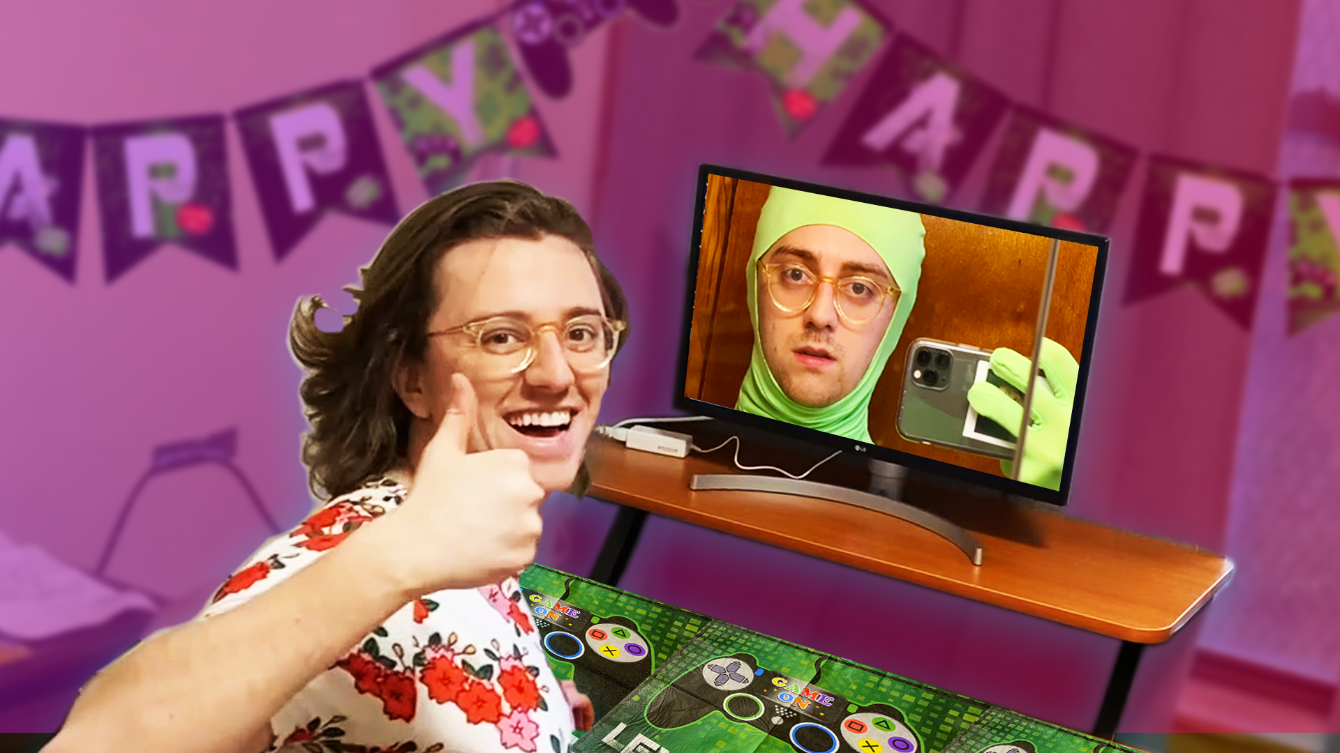 Brian David Gilbert gives a thumbs up while he sits at a desk covered in a video game themed tablecloth. On the monitor is another picture of Brian wearing a green screen suit
