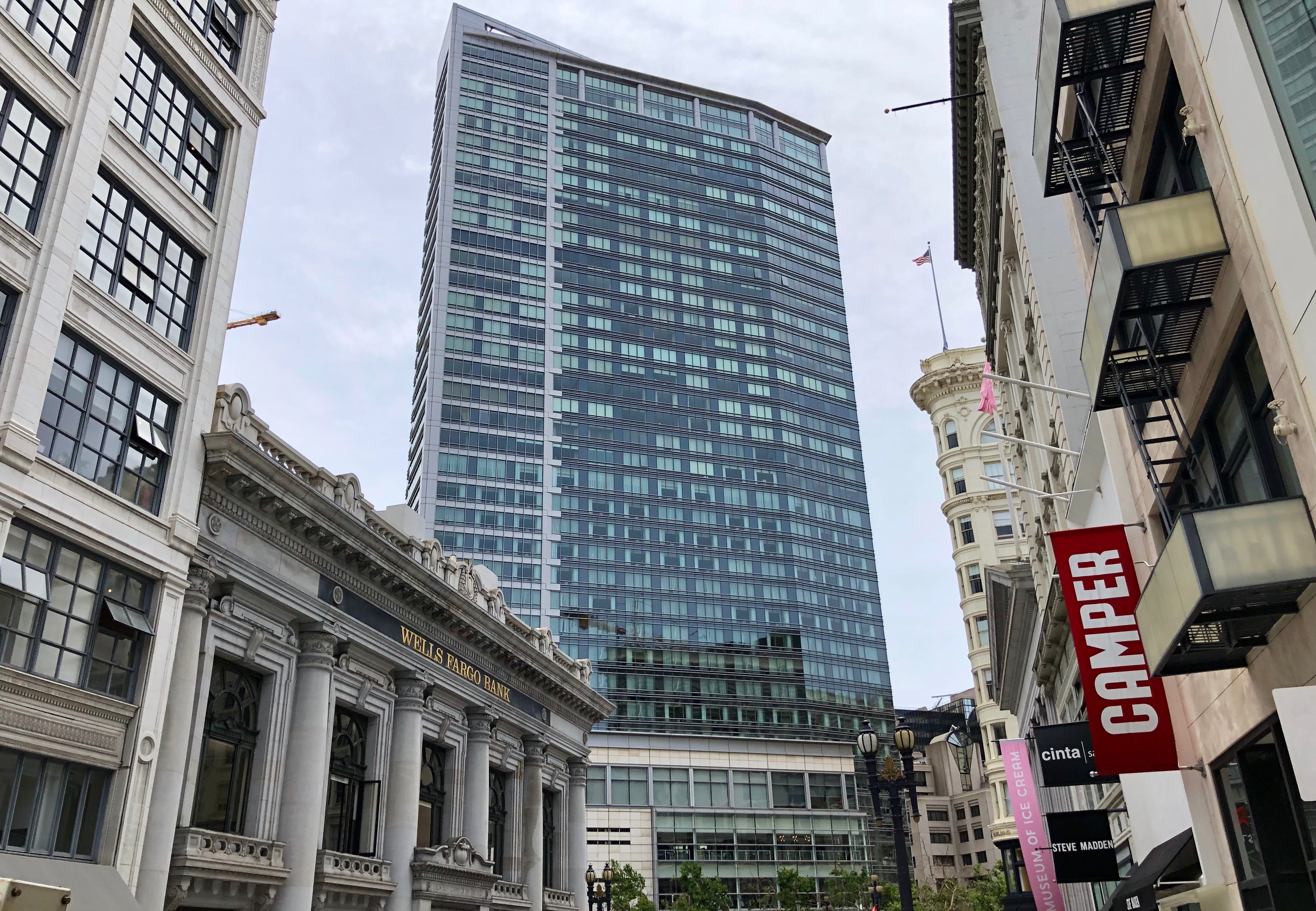 A gleaming, gray high-rise with a glass wall sits at the end of a street in a financial district.