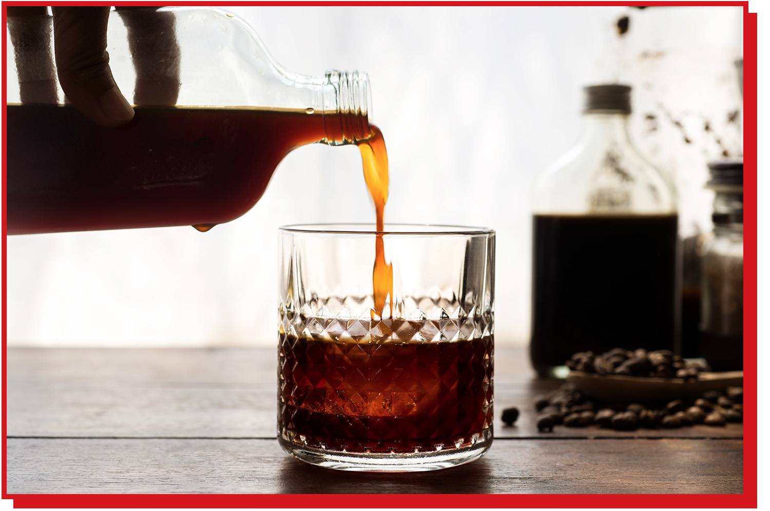 Coffee being poured from a clear glass bottle into a short glass.