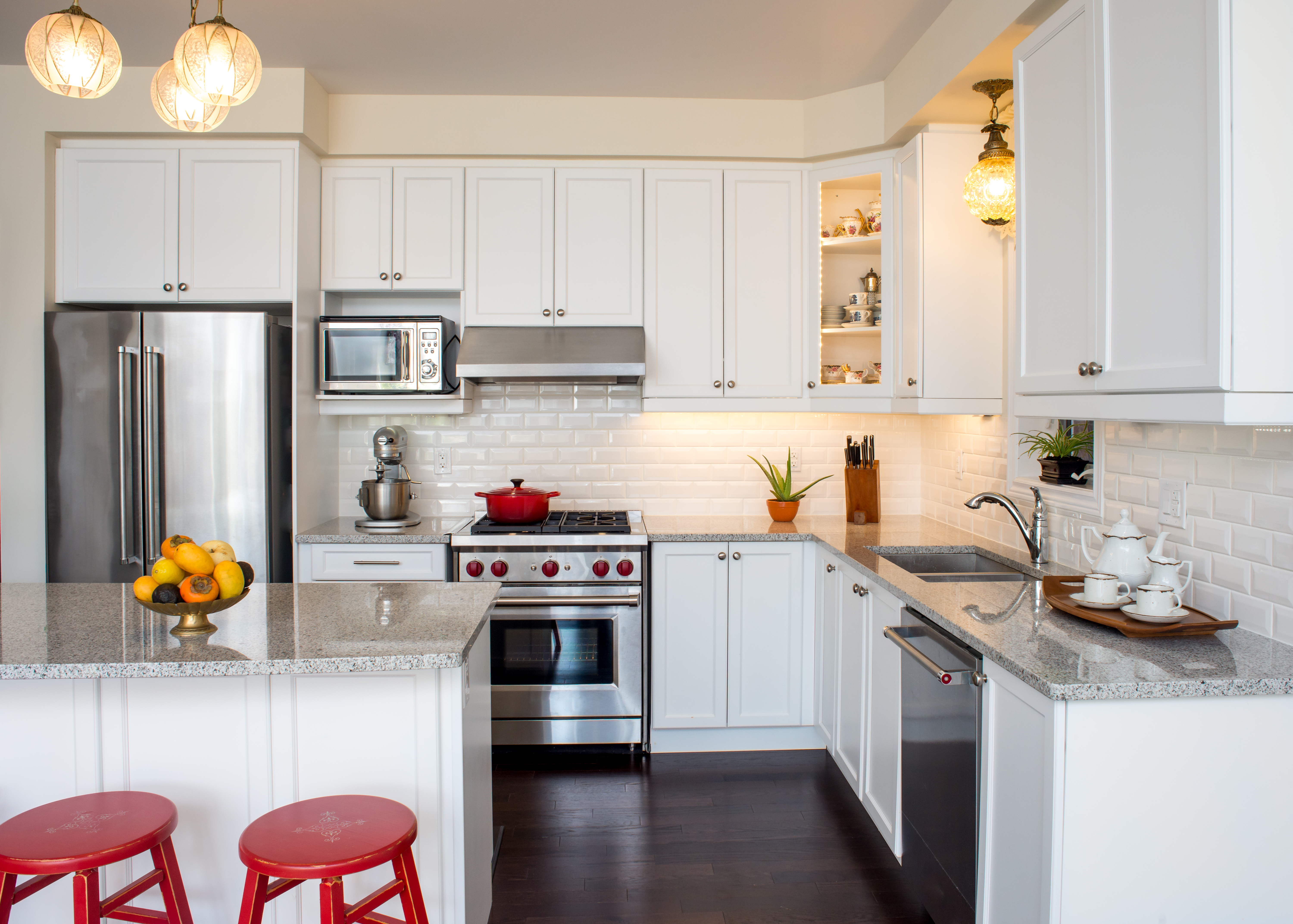 white kitchen with red accents and red stools