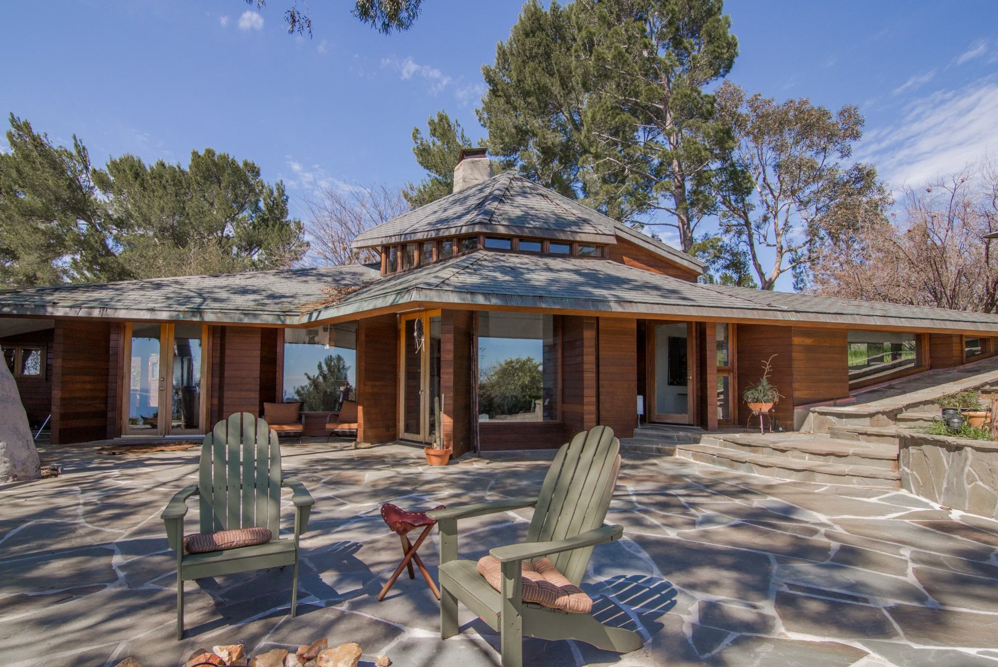 Low-slung home with redwood siding, large glass windows, and large patio.