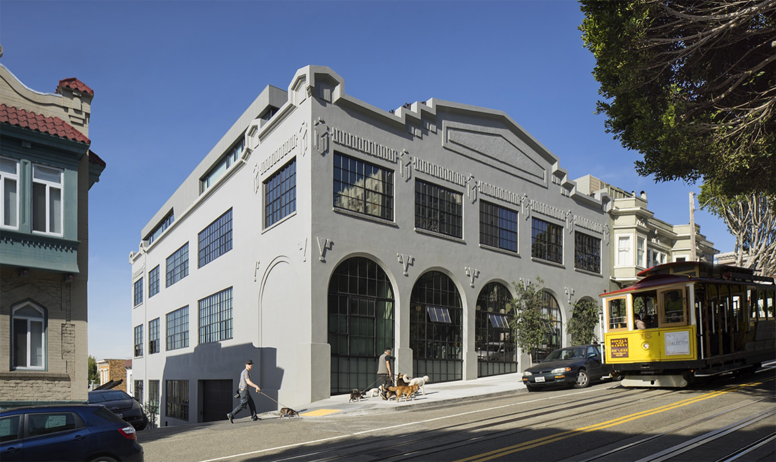The facade of a concrete, two-story building on a sunny day, with arched windows and a San Francisco cable car running on the street.