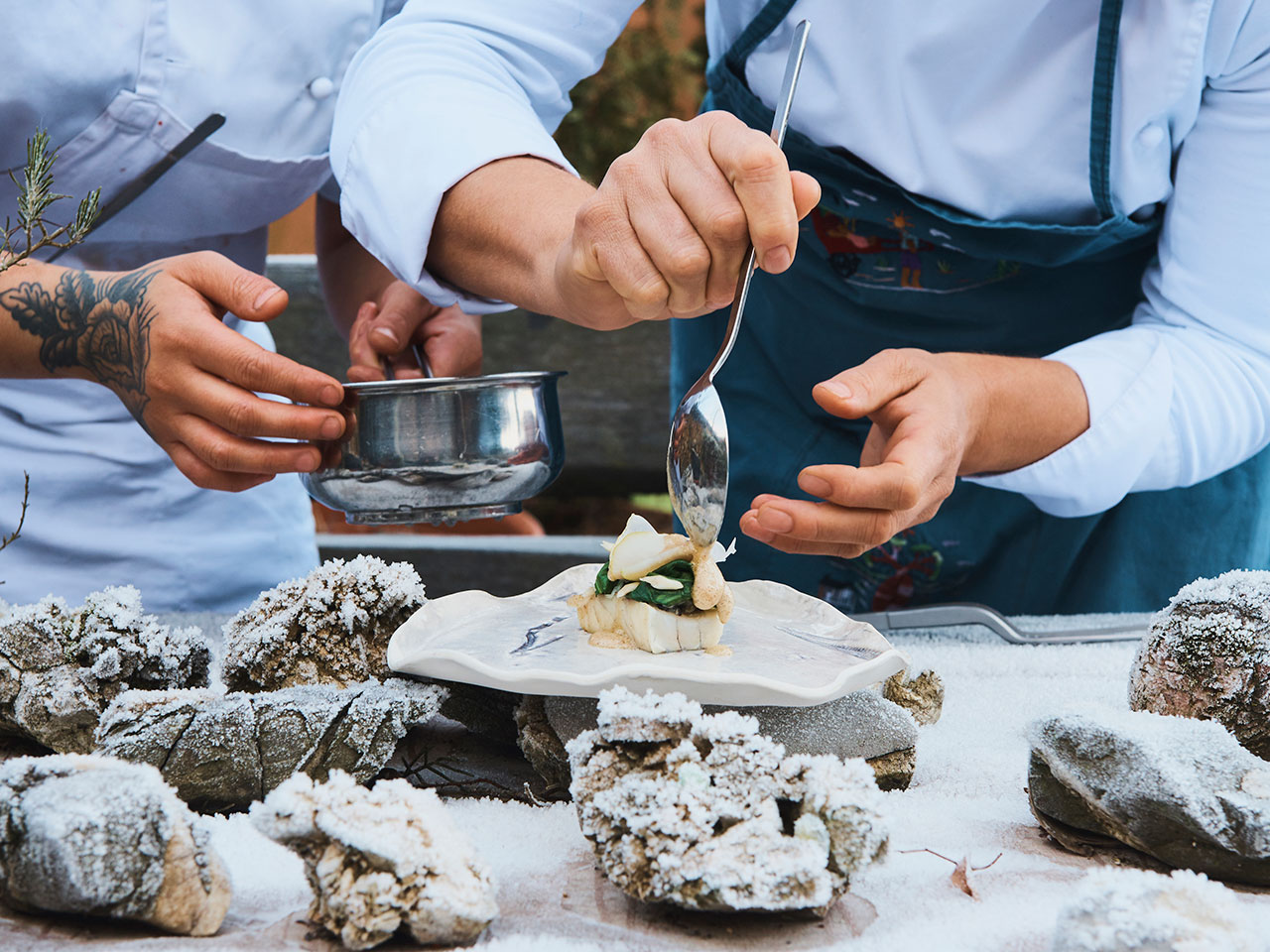 Two chefs plate a fish dish
